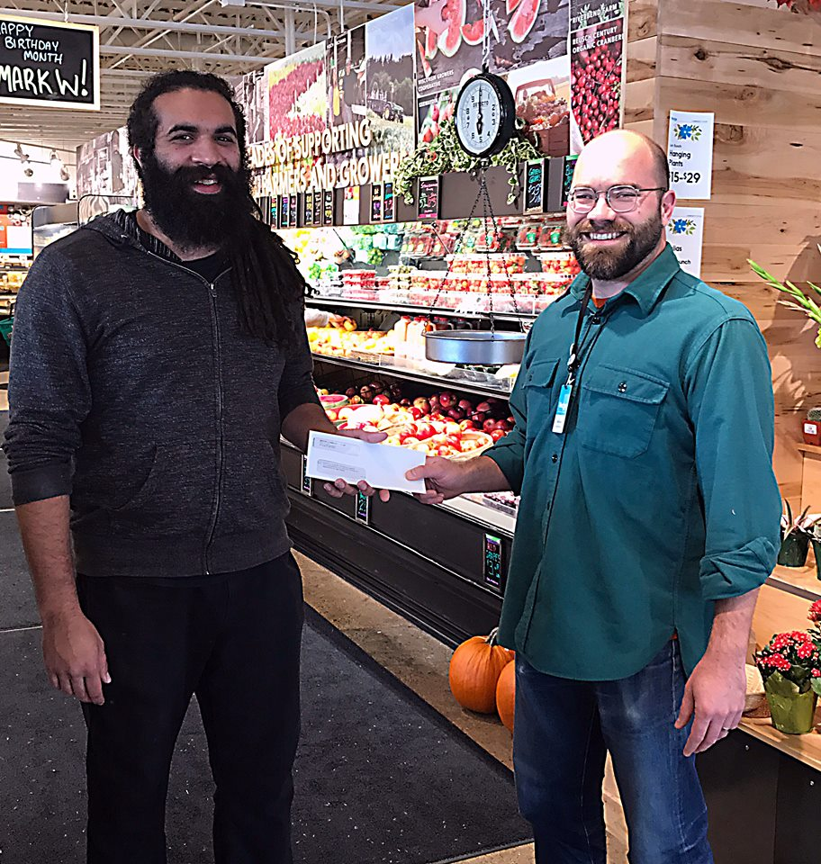 Canvass Coordinator Peter Randol receives round-up check from Manager Matthew.