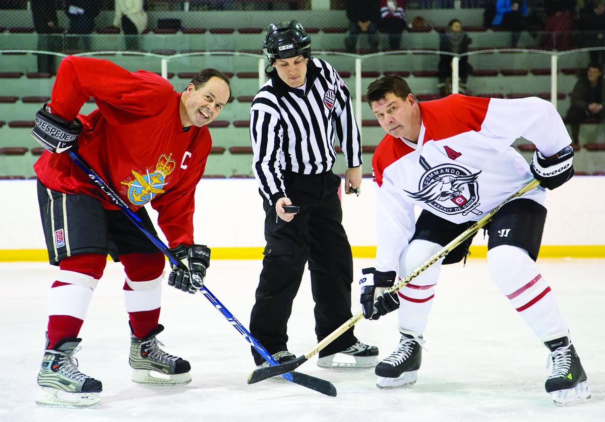 Facing off for Canadian military members and their families: GOFO captain Gen. Tom Lawson, left, and Esprit de Corps publisher Scott Taylor, Captain of the Commandos, ready for the puck to drop in the January 2014 game.