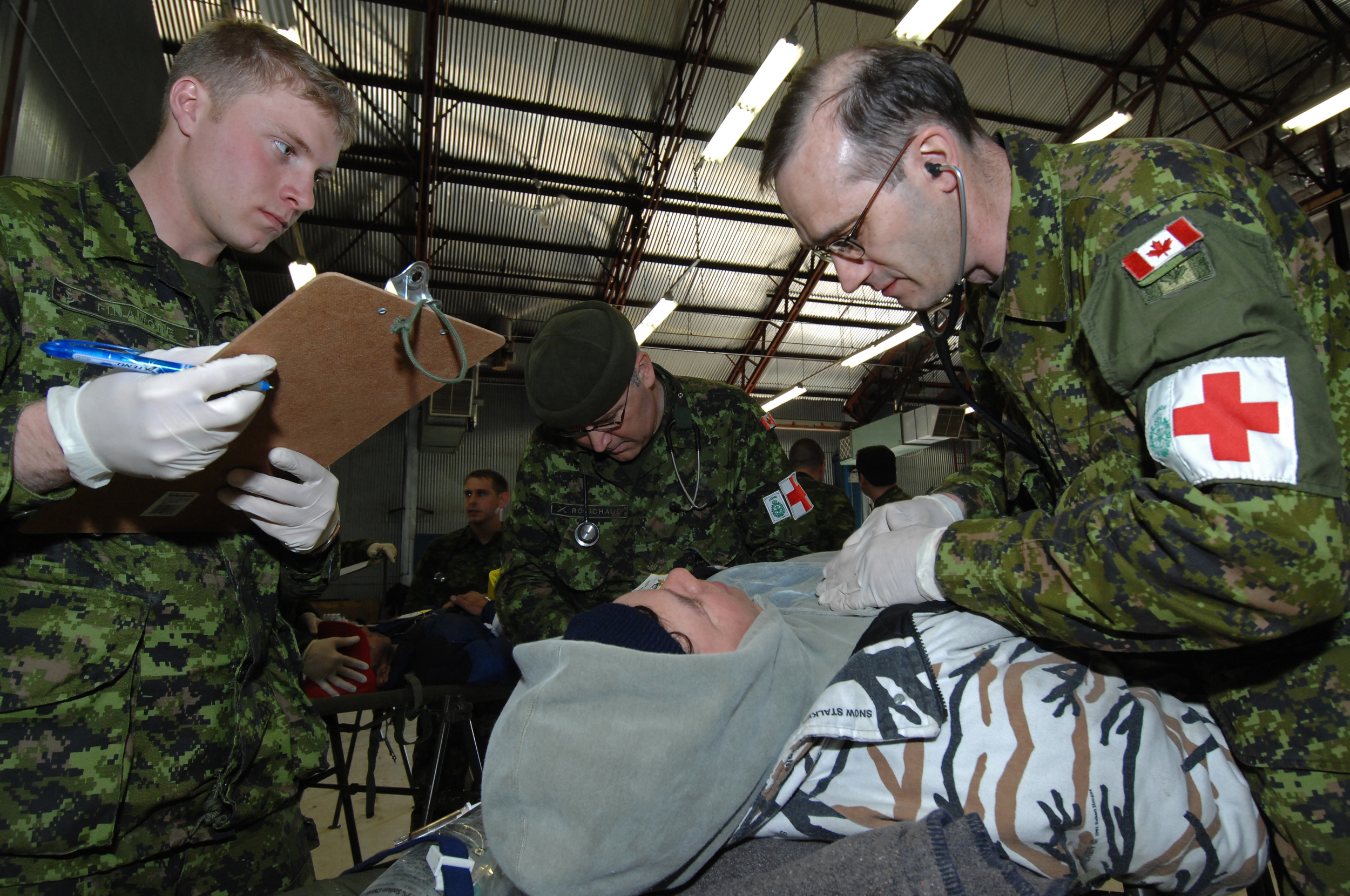 Physician assistant Master Warrant Officer Lorne Turner (right) and medical technician Master Corporal Richard Robichaud (centre) of 2 Field Ambulance in Petawawa, Ontario, examine Ranger Robert Buckle of Aklavik, Northwest Territories, as medical technician Ordinary Seaman Dave Finamore records their findings.