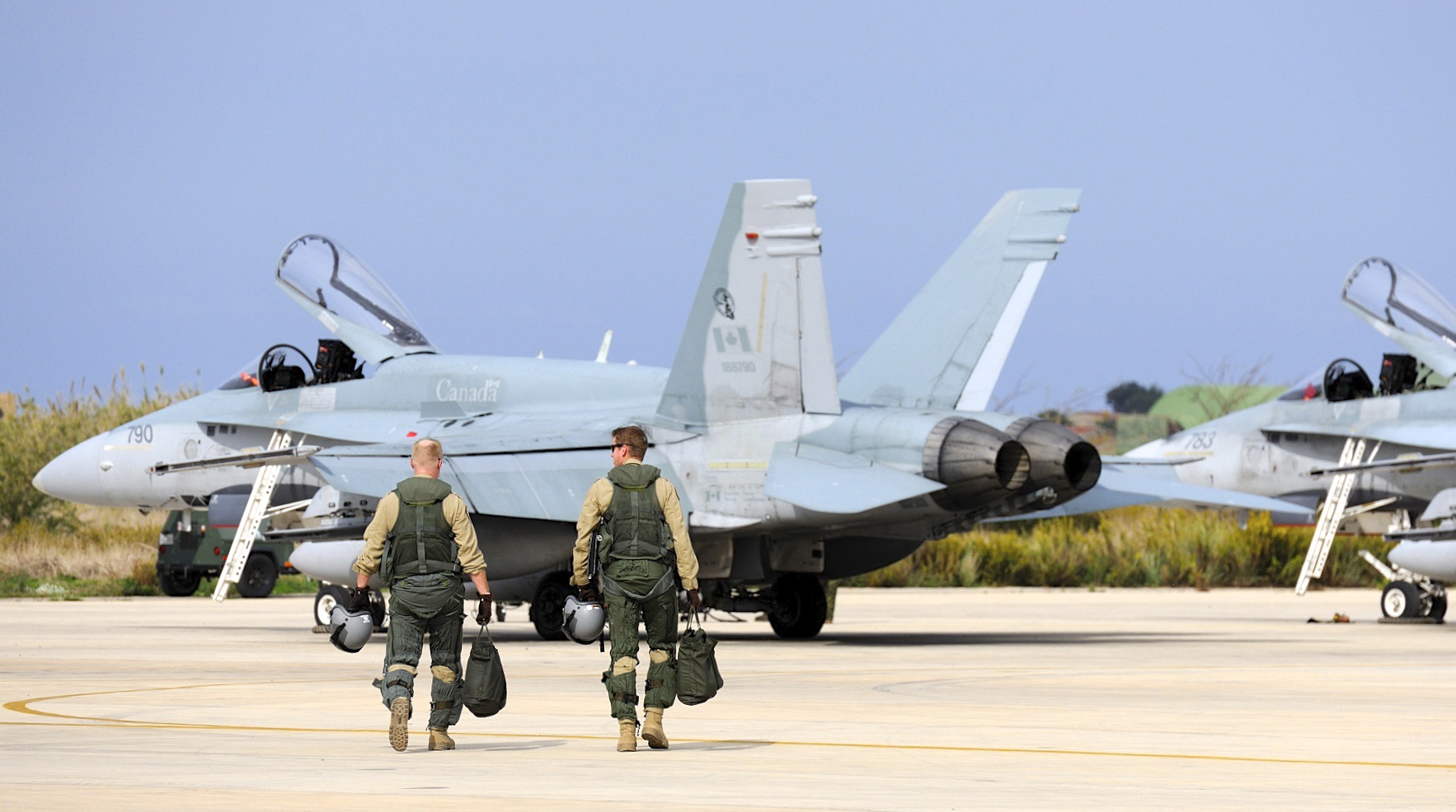 Two CF-18 Hornet pilots make their way to the flight line to return to Canada from Trapani, Italy on November 2, 2011. The Canadian pilots flying sorties over Iraq as part of Operation IMPACT adhere to a strict routine, working on a 24-7 rotation. (Combat Camera).