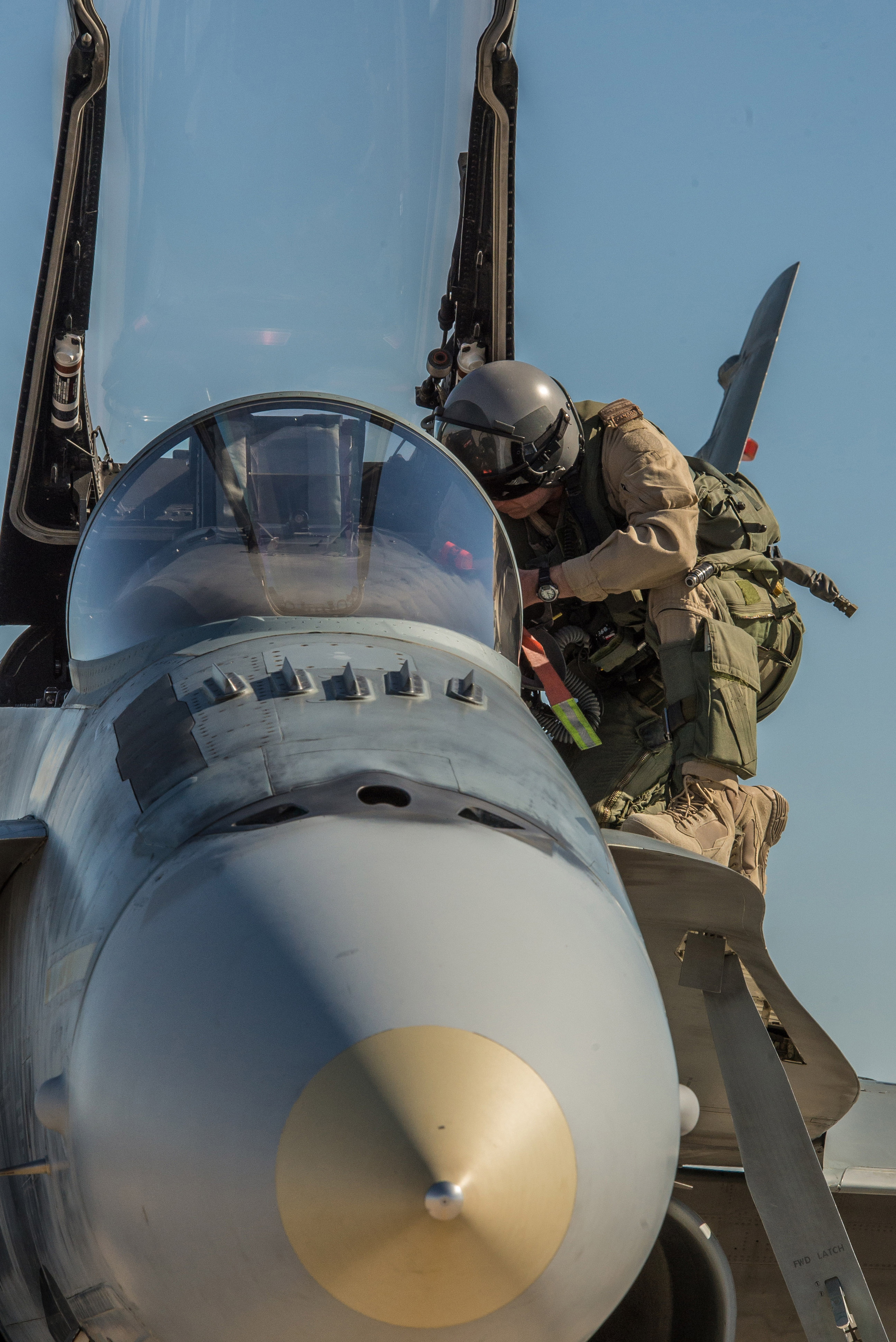 A pilot prepares the cockpit of his CF-18 Hornet before his next mission during Operation IMPACT in Kuwait, on February 8, 2015. (Combat Camera).