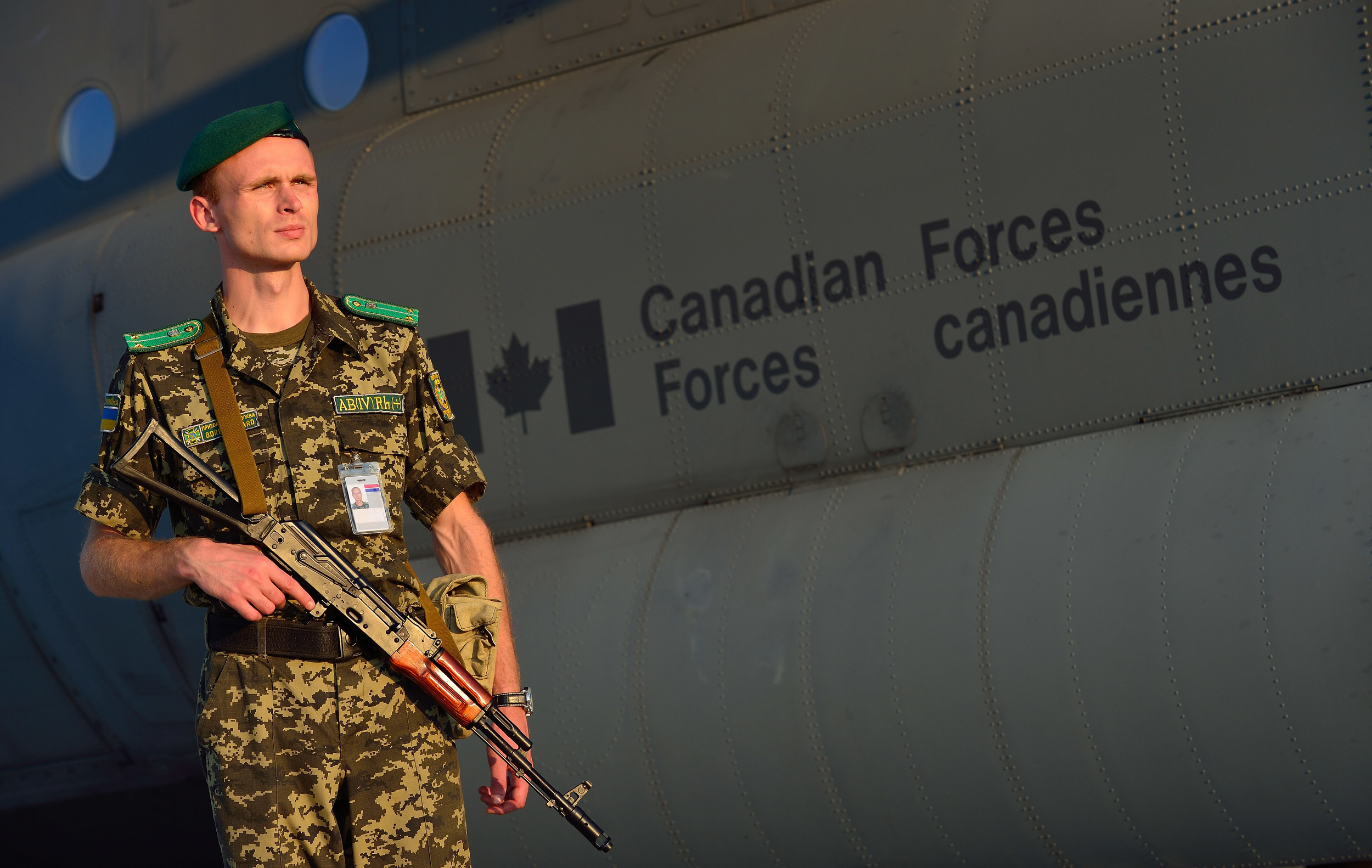 A Ukrainian soldier stands watch at Boryspil International Airport as equipment from a Canadian CC-130J Hercules aircraft from 436 Transport Squadron in Trenton, Ontario is unloaded on August 8, 2014. (Combat Camera).