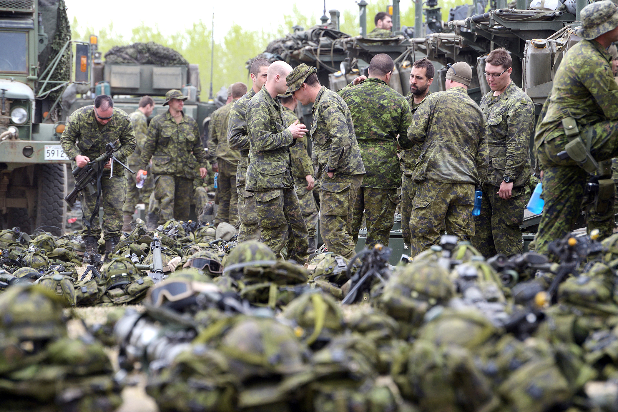 """Canadian soldiers from the Royal 22nd Regiment check their equipment during Ex MAPLE RESOLVE. The huge training exercise is played out over 62,000 hectares at CFB Wainwright, Alberta. During the exercise, the Royal 22nd Regiment retook land that had been """"overrun"""" by enemy forces, in an elaborate narrative that included the use of mock villages, as well as soldiers and civilian actors portraying refugees, village leaders, and military officials. (Sgt Dan Shinouinard, DND)"""