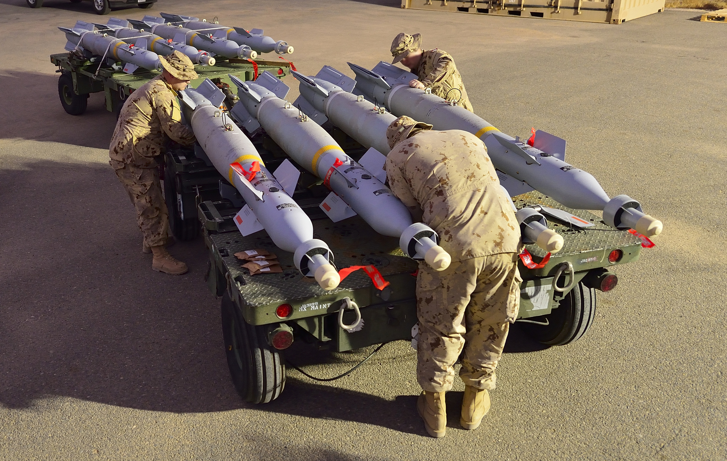 """Canadian Armed Forces Ammunition Technicians in Kuwait assemble 500-pound guided bombs that will be mounted on CF-188 Fighter jets flying combat missions over Iraq during Operation IMPACT on October 31, 2014 . The RCAF would like to acquire low-collateral damage weapons (LCDW) for use in targeted missions over cities and """"politically sensitive operations"""" to cut down on the likelihood of collateral damage. (DND)"""