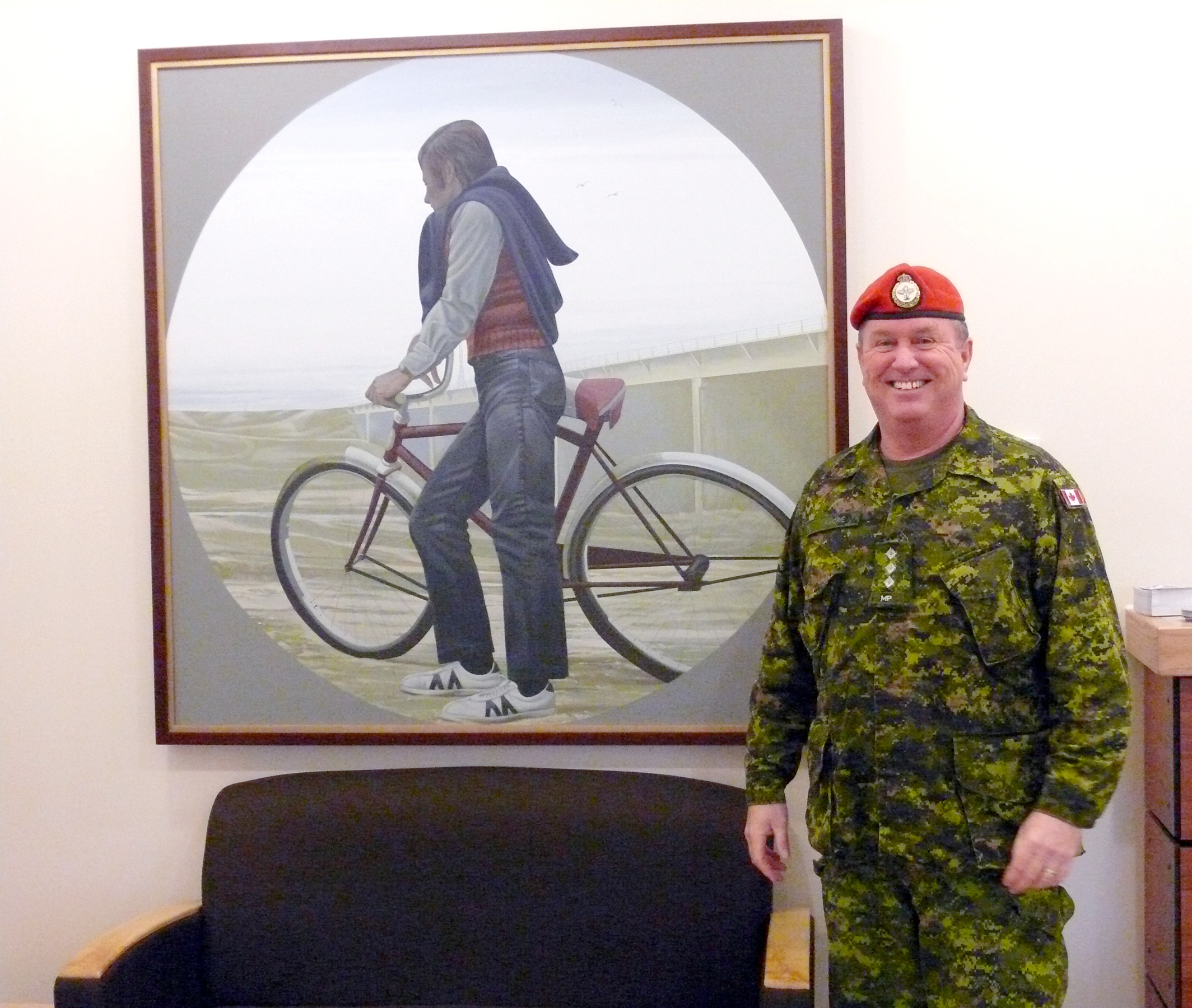 Captain K.B. Lamorie stands before one of the paintings from the Canada Council Art Bank currently on display at the transition centre at CFB Petawawa. This initiative by Her Excellency Sharon Johnston, who graduated from the University of Toronto as a physical and occupational therapist, is bringing little-seen paintings and sculptures into a traditionally austere environment in an effort to help CAF members dealing with PTSD. (esprit de corps)