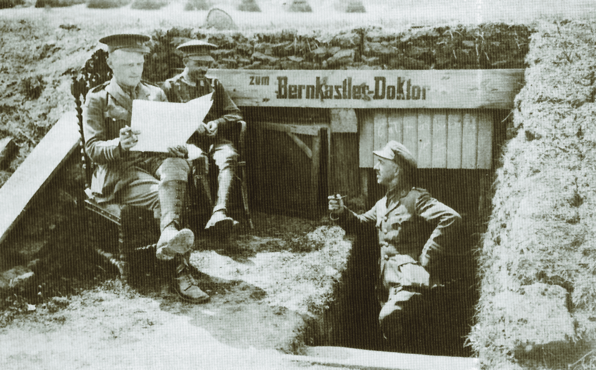 British officers outside a captured and well camouflaged German dressing station during the First World War. During quiet times, officers and enlist3ed men alike took advantage to write letters home, read trench newspapers, and smoke a pipe. (Imperial War Museum)