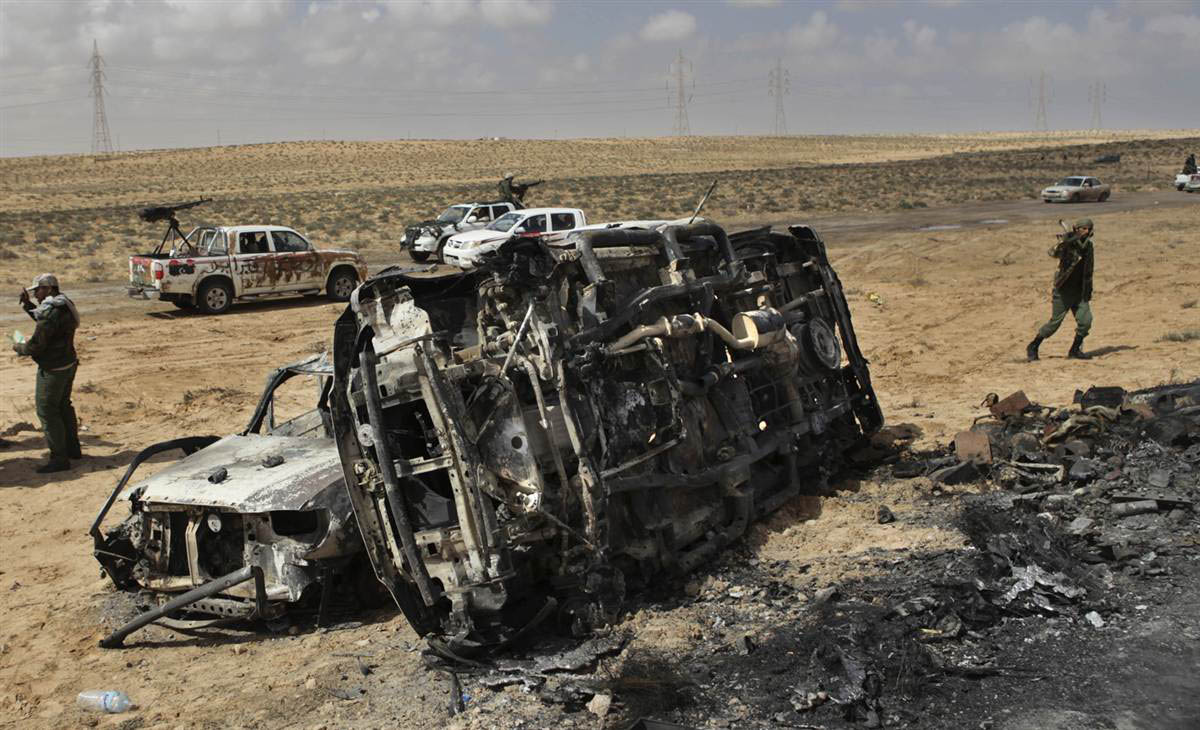 A Libyan rebel walks on past the charred remains of vehicles that were hit by NATO airstrike near Brega.