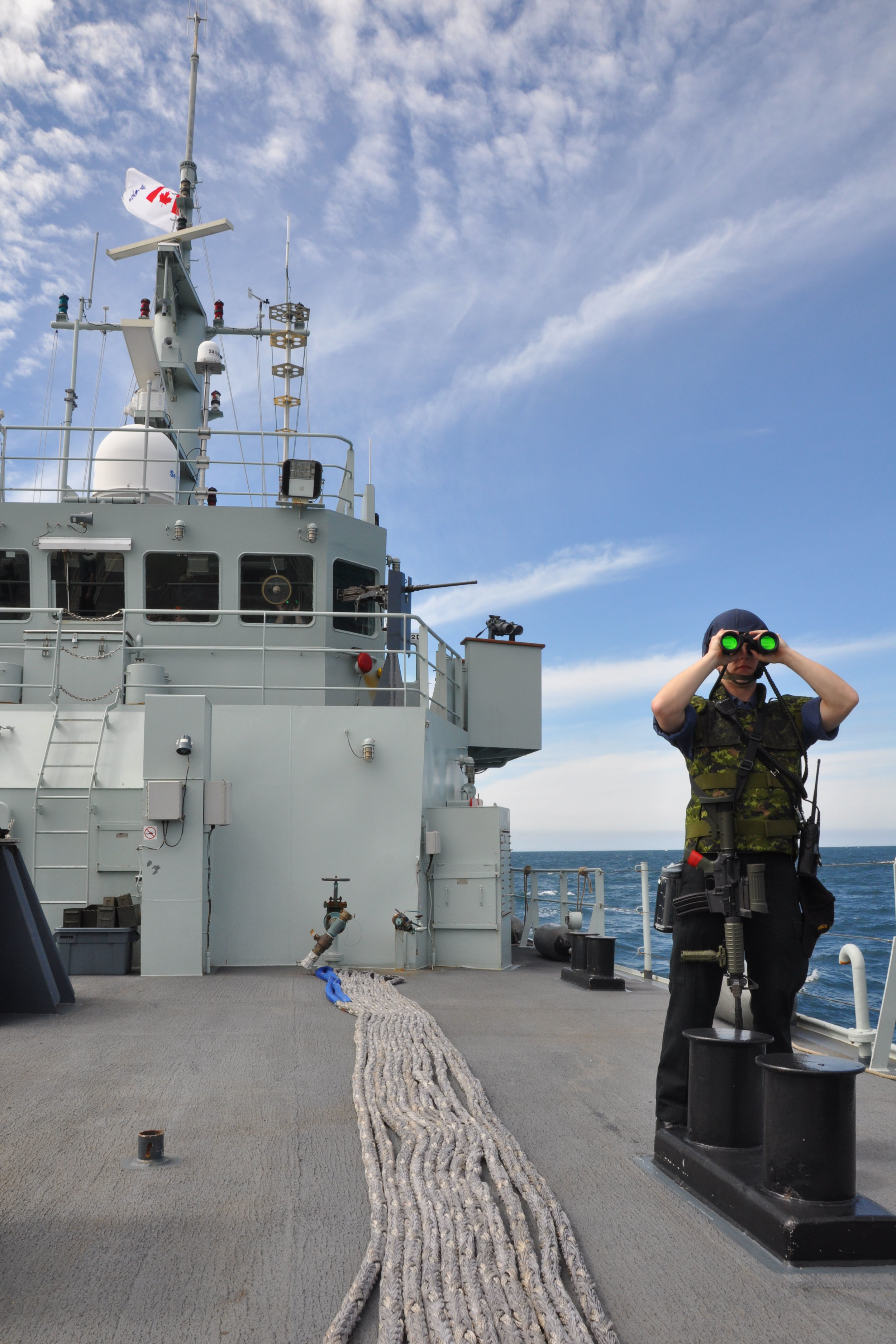A crew member of HMCS Saskatoon conducts force protection when approaching the harbour of Ensanada, Mexico on March 5, 2016 during Operation CARIBBE. Canada contributes ships and CP-140 Aurora aircraft to the joint interagency effort to prevent illicit trafficking in the Caribbean sea, the eastern Pacific Ocean, and the coastal waters of Central America. (DND)
