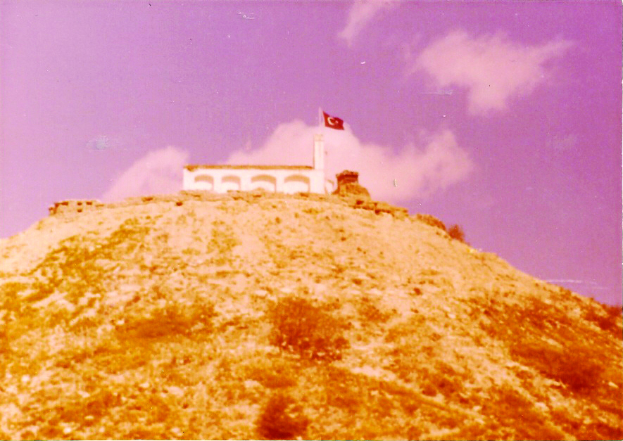 The church at the top of the mountain that had been turned into a machine-gun nest by the Turkish army. The gun emplacements on the left and right in front of the church are visible, as is the Turkish flag flying above. We watched them while they watched us. (Frank Reid)