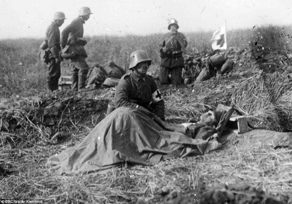 Final moments: Walter was just 16 when he fought at the Somme but his photos soon took on dark tone. Here he captures a German army medic kneeling beside a dying colleague - but he can do no more than offer comfort photographs taken by German soldier Walter Kleinfeldt who fought at the Somme aged just 16.