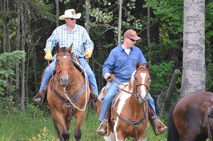 Canadian Ranger Robert Catto (left) from 100 Mile House Patrol and Corporal Edward MacDonald from 17 Service Battalion steer their horses through the woods in Quesnel, BC during Exercise Choke Apple 2016. Photo by Captain Chris Poulton, Public Affairs Officer, 4 CRPG