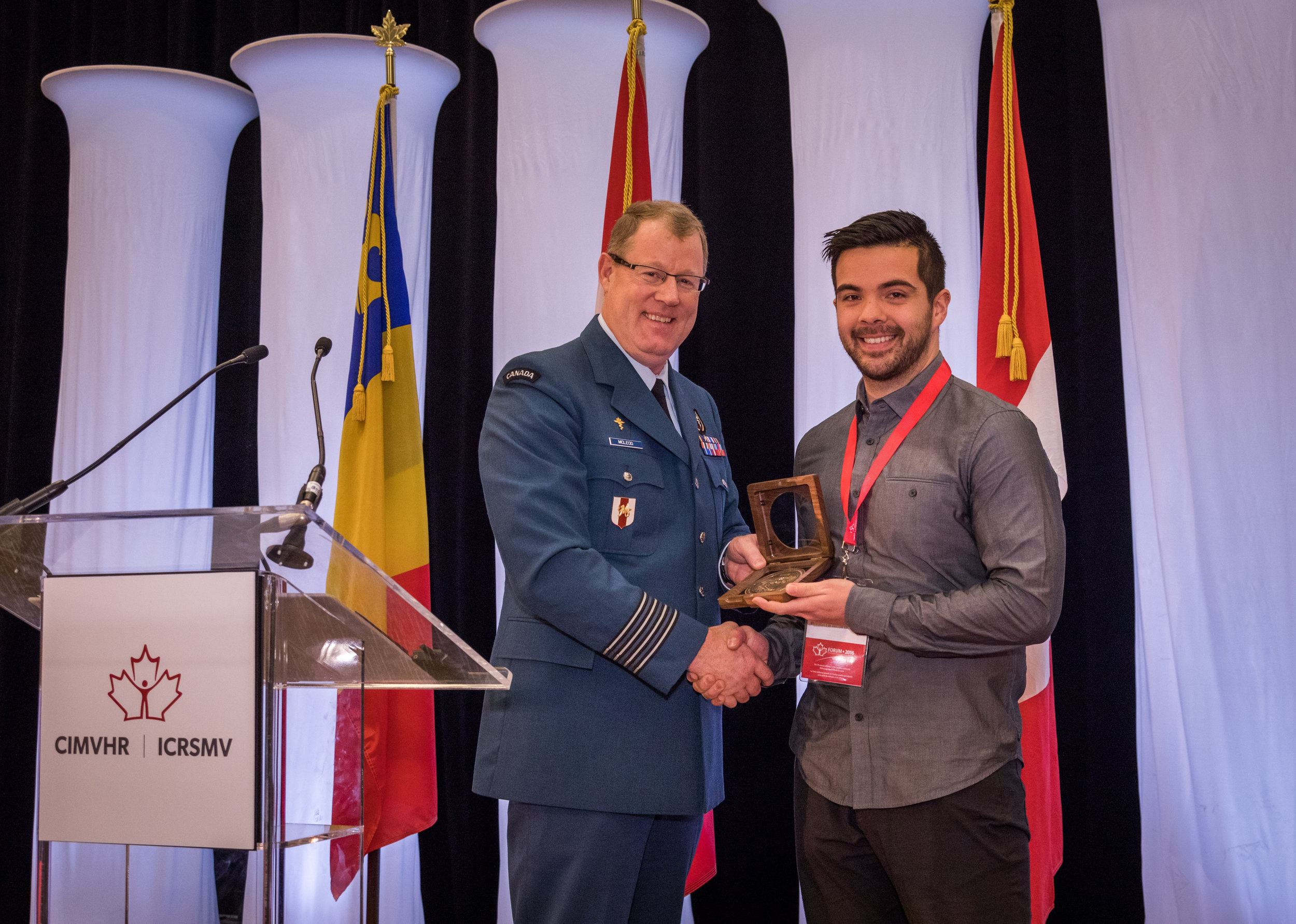 Colonel Scott McLeod, Deputy Surgeon General, presents the Banting Award to Mr. James Baylis accepting on behalf of Dr. Christian Kastrup, professor at UBC, for his research on self-propelled particles.