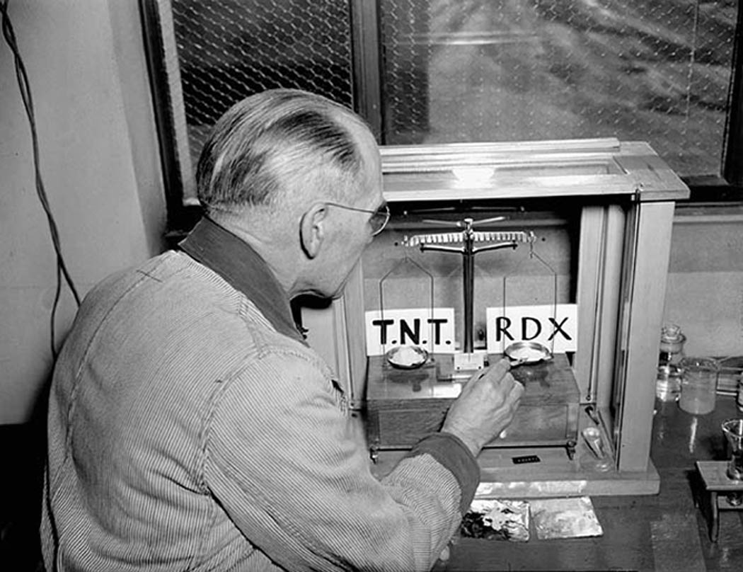 : Scientist Norman Randall weighs ten ounces of TNT and ten ounces of RDX explosives on a scale prior to ballistics tests to compare the power of the two explosives at the National Research Council explosives laboratory, March 1944. (library and archives canada,   3197143