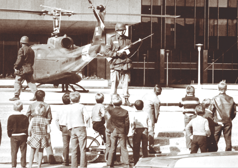 A group of children gather in front of Montreal's Quebec Provincial Police headquarters to see armed soldiers and an Iroquois helicopter policing the area against terrorists during the 1970 October Crisis after the War Measures Act was instated. The suspension of civil liberties in Quebec was politically controversial. When the crisis was over, Prime Minister Pierre Trudeau pledged to refine and limit the application of the Act in internal crises, but by the time of the defeat of the final Trudeau government in 1984, the Act had not been modified. Not until 1988 was the War Measures Act repealed and replaced by the Emergencies Act, which created more limited and specific powers for the government to deal with security emergencies. (lac/pa-129838)