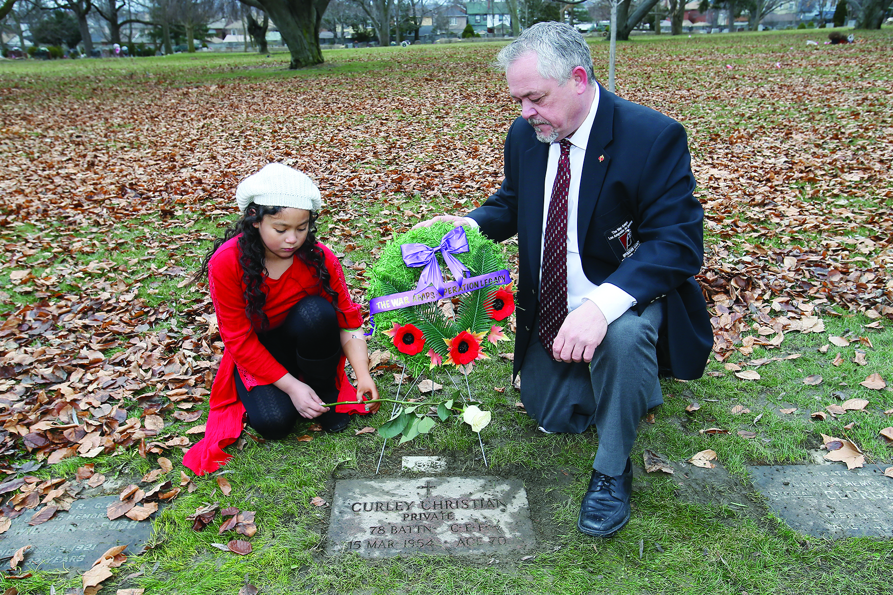 Rob Larman, a leg amputee, and Tiffany Ross, a left arm amputee and member of The War Amps Child Amputee (CHAMP) Program, lay a rose at the grave of Curley Christian, who lost all four limbs at Vimy Ridge, at Prospect Cemetery in Toronto, Ontario. Christian died on March 15, 1954 at 70 years of age. (john e. sokolowski, war amps)