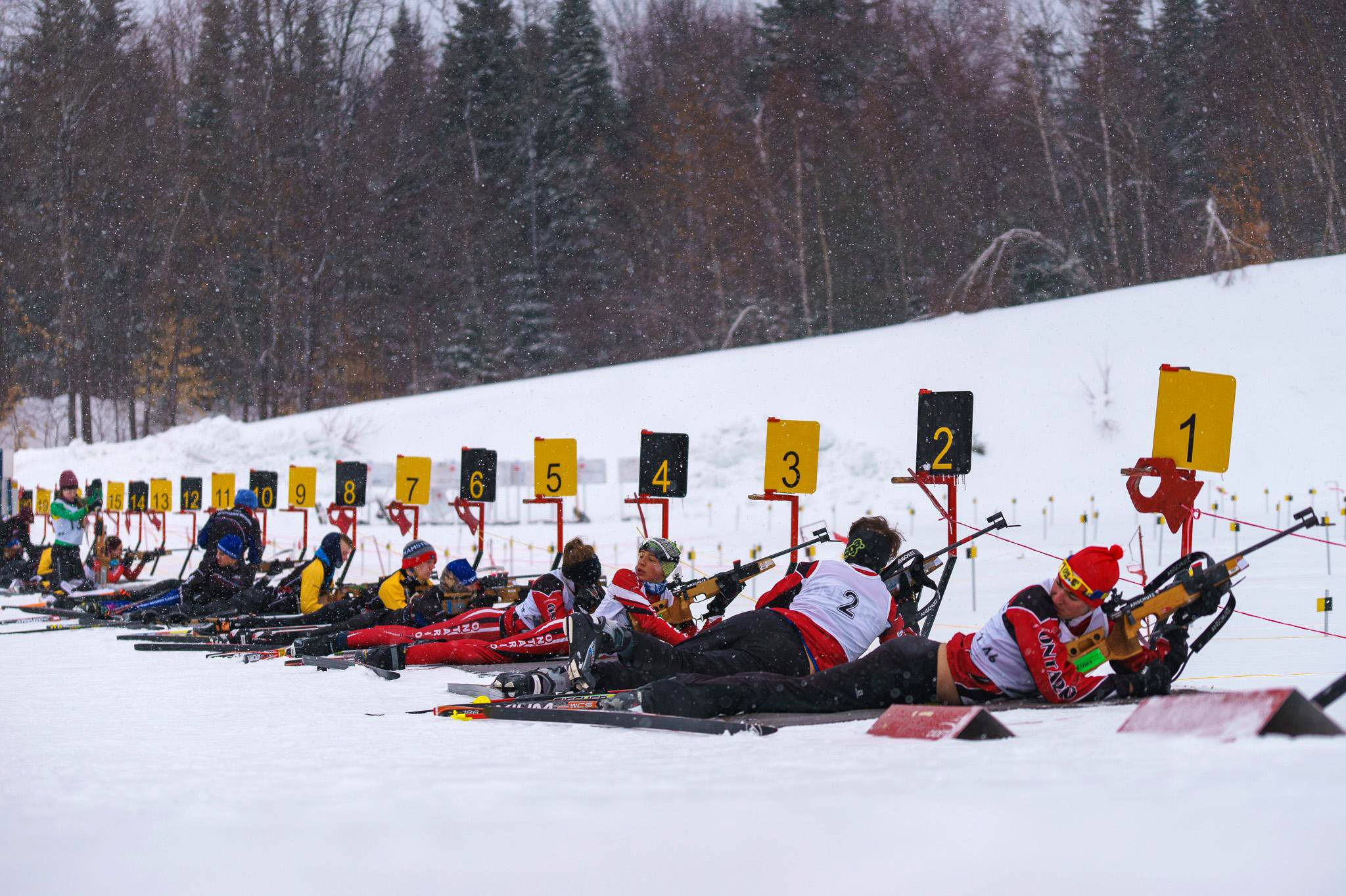 Cadet biathletes, some from Team Ontario (firing lanes 1 to 4), shoot during the sprint race event.