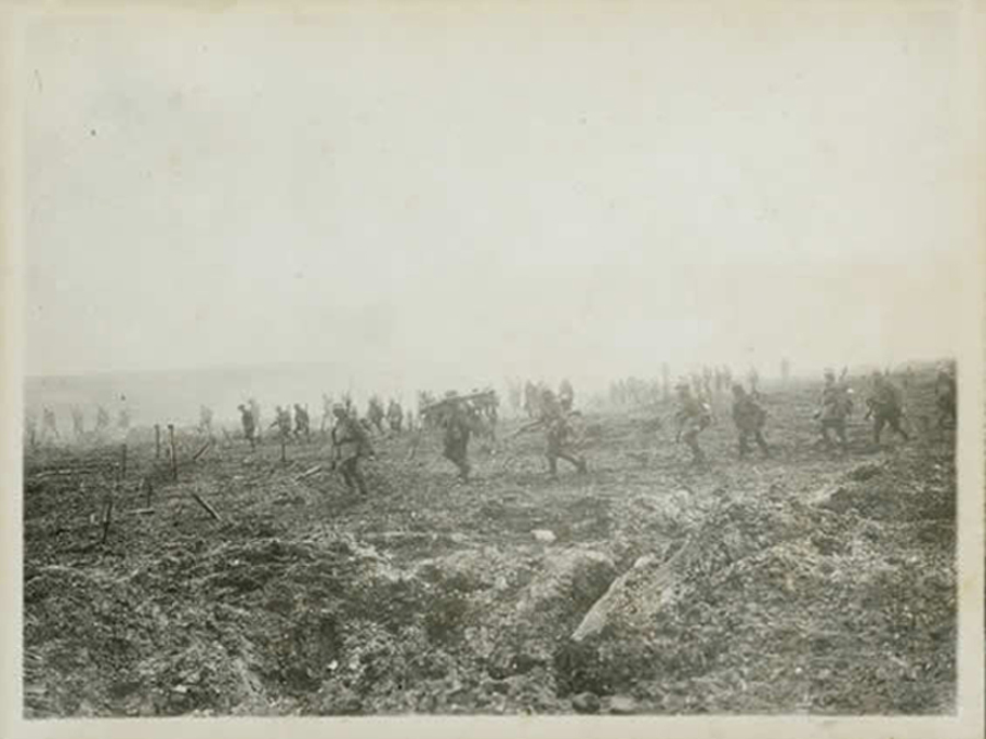 Canadians of the 29th Infantry Battalion advance across no man's land through the German barbed wire during the Battle of Vimy Ridge, April 1917. Most soldiers are armed with their Lee Enfield rifles, but the soldier in the middle carries a Lewis machine-gun on his shoulder. (dnd, george metcalf archival collection, cwm   19920085-915  )