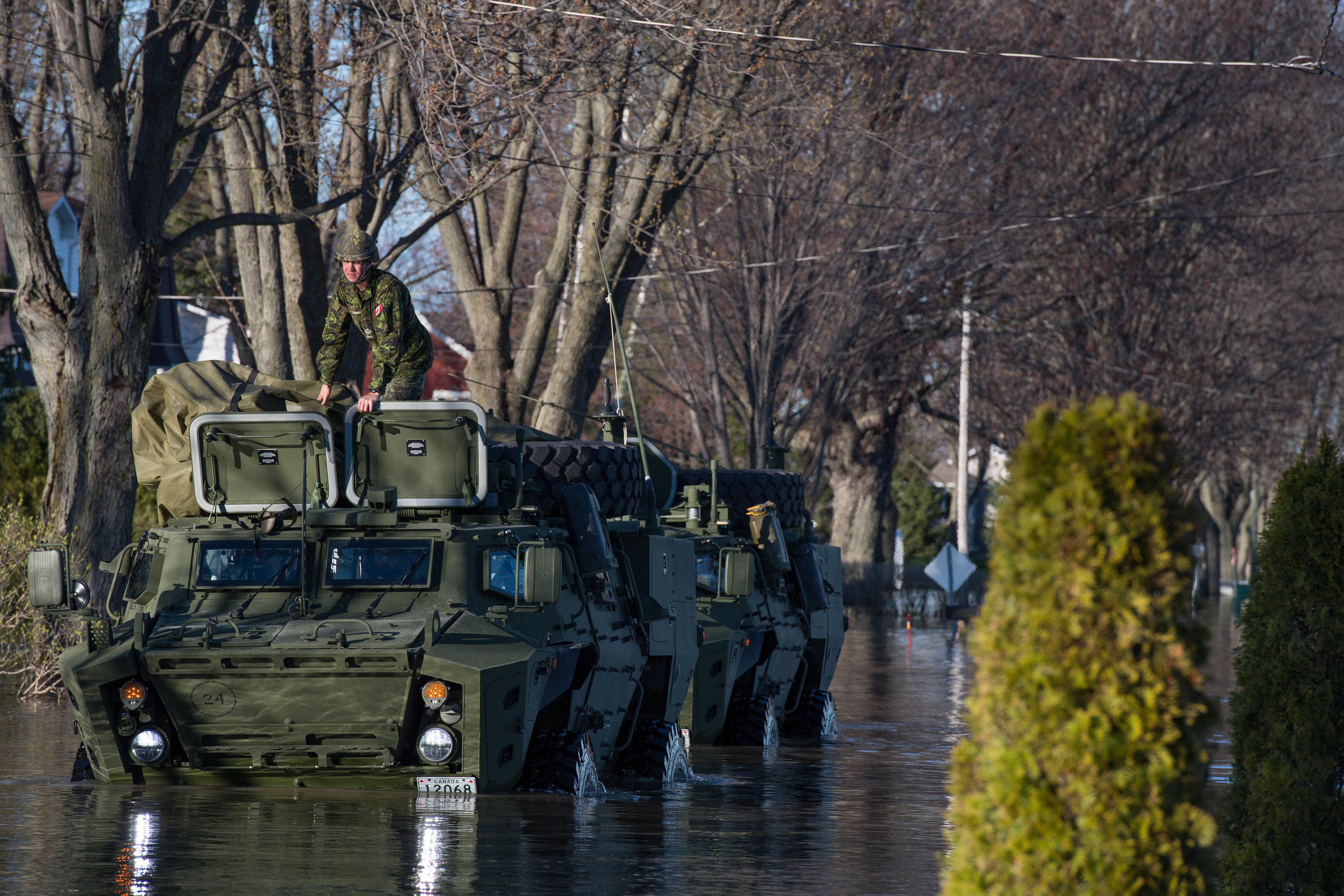 Tactical Armoured Patrol Vehicles patrol flooded streets in Saint-Barthélemy, Québec during Operation LENTUS, May 12, 2017. The TAPV, which replaces the RG-31 Nyala, is now being delivered to the Canadian Army. Under the Defence Acquisition Guide (DAG), the Army will also receive simulators for the LAV 6.0, Leopard 2 main battle tank and TAPV. (sgt marc-andré gaudreault, valcartier imaging services)