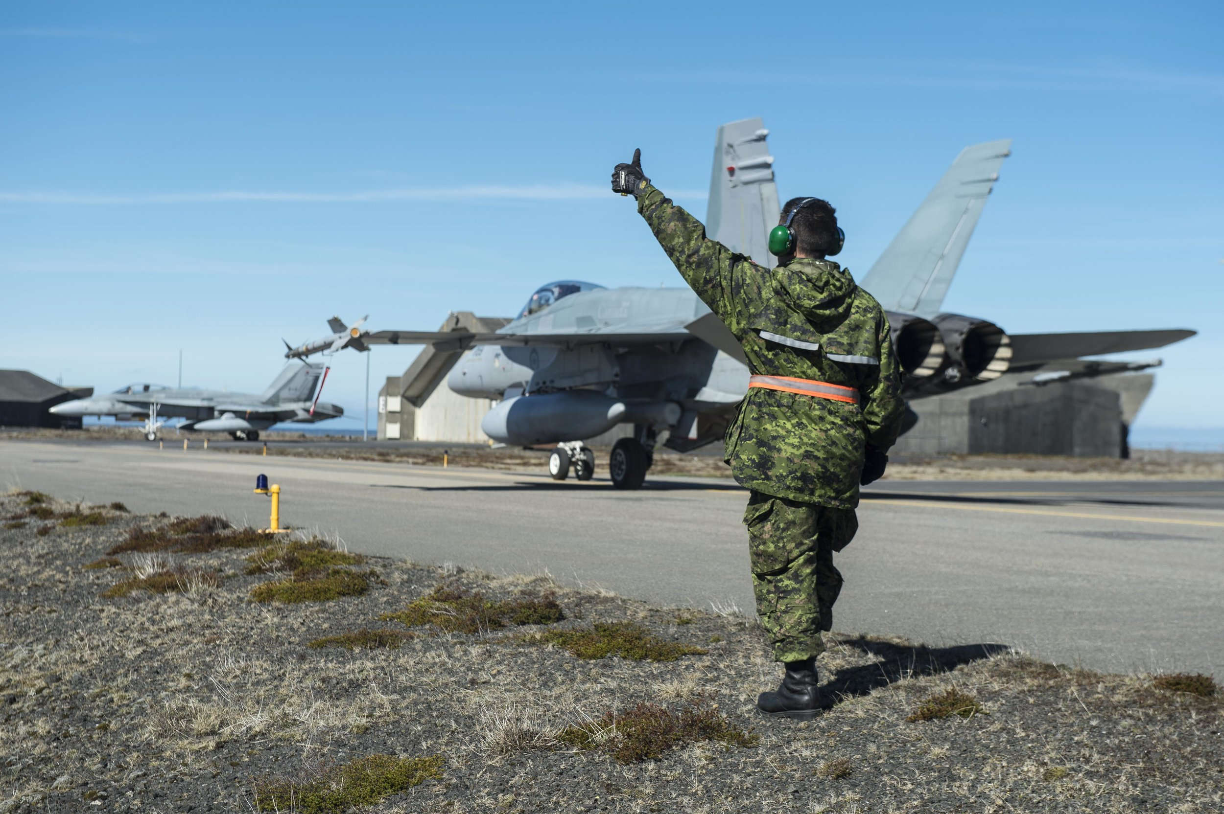 "Weapons technician, Cpl Chad Doley-Bourget indicates a thumbs up for the CF-188 Hornet to return to the hangar in Keflavik, Iceland during Operation REASSURANCE, May 19, 2017. According to the Liberal's Defence Review, ""Canada will procure a fighter capability of 88 jets to replace the aging CF-18 fleet"" in order to meet NATO and NORAD commitments. (Cpl Gary Calvé, ATF Iceland)"