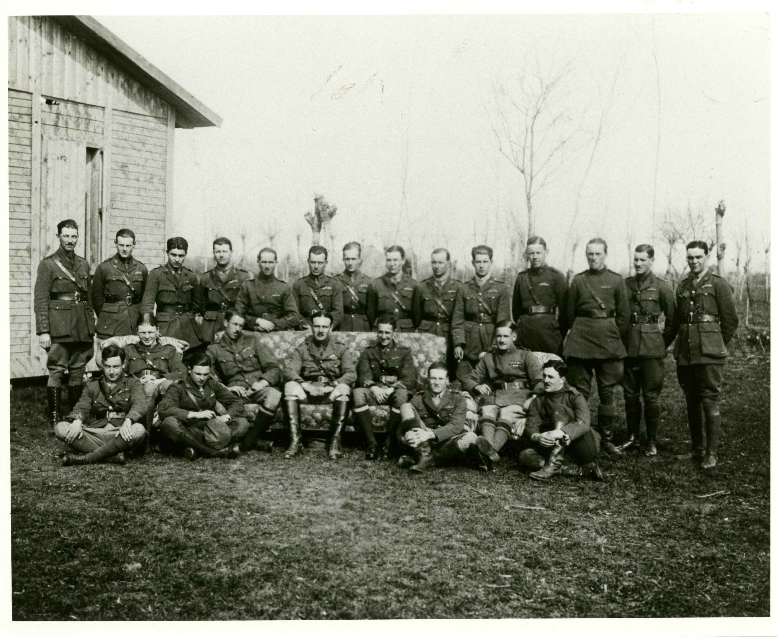 """Of the pilots of No. 66 Squadron RFC photographed at San Pietro in Gu in March 1918, Birks remembered the following: standing, second from left, Lt. Christopher McEvoy (9 victories); third, 2nd Lt. Charles C. Robinson; fifth, Lt. Francis S. Symondson (13), sixth, 2nd Lt. Herbert N.E. Row (3), seventh, 2nd Lt. Robert G. Reid (3), ninth, 2nd Lt. Henry B. Homan (killed in crash, 4 April 1918), twelfth, 2nd Lt. Gordon F. Mason Apps (10); and thirteenth, 2nd Lt Gerald A. Birks (12). Seated, first from left, 2nd Lt. Norman S. Taylor (3), second, Captain William Topham, recording officer, third, 2nd Lt. Stanley Stanger (13 victories), fourth, Capt. John W. Warnock, """"my first flight commander"""" (1), fifth, Maj. John TudorPowell Whittaker, squadron CO; sixth, Capt. Hilliard Brooke Bell (9), seventh, 2nd Lt. Alan Jerrard, who on 30 March was taken prisoner in an action that earned him the only Victoria Cross awarded to a Camel pilot (7); eighth, Capt. Peter Carpenter (24); and Lt. Harold R. Eycott-Martin (8). (gerald birks album, courtesy jon guttman)"""