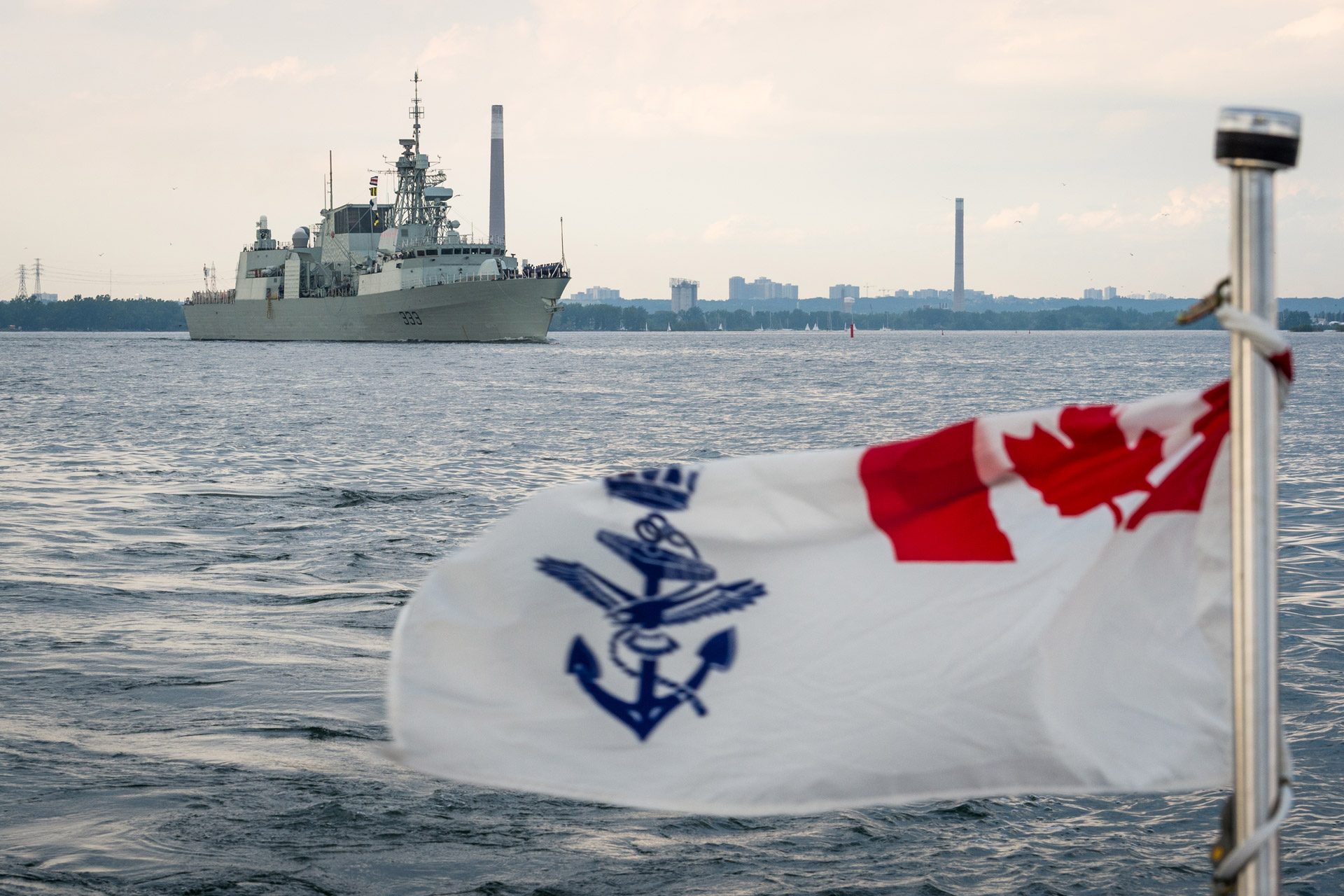 The Naval Ensign on the back of a rigid hull inflatable boat flies as HMCS Toronto leaves her namesake port during Canada 150 celebrations. Until the CSC's arrival, the RCN's 12 Halifax-class vessels will be serving as the backbone of the Navy. As such, the fleet has undergone a modernization of its combat systems and a mid-life refit to ensure the frigates remain effective throughout their service life. (cpl kenneth galbraith, dnd)