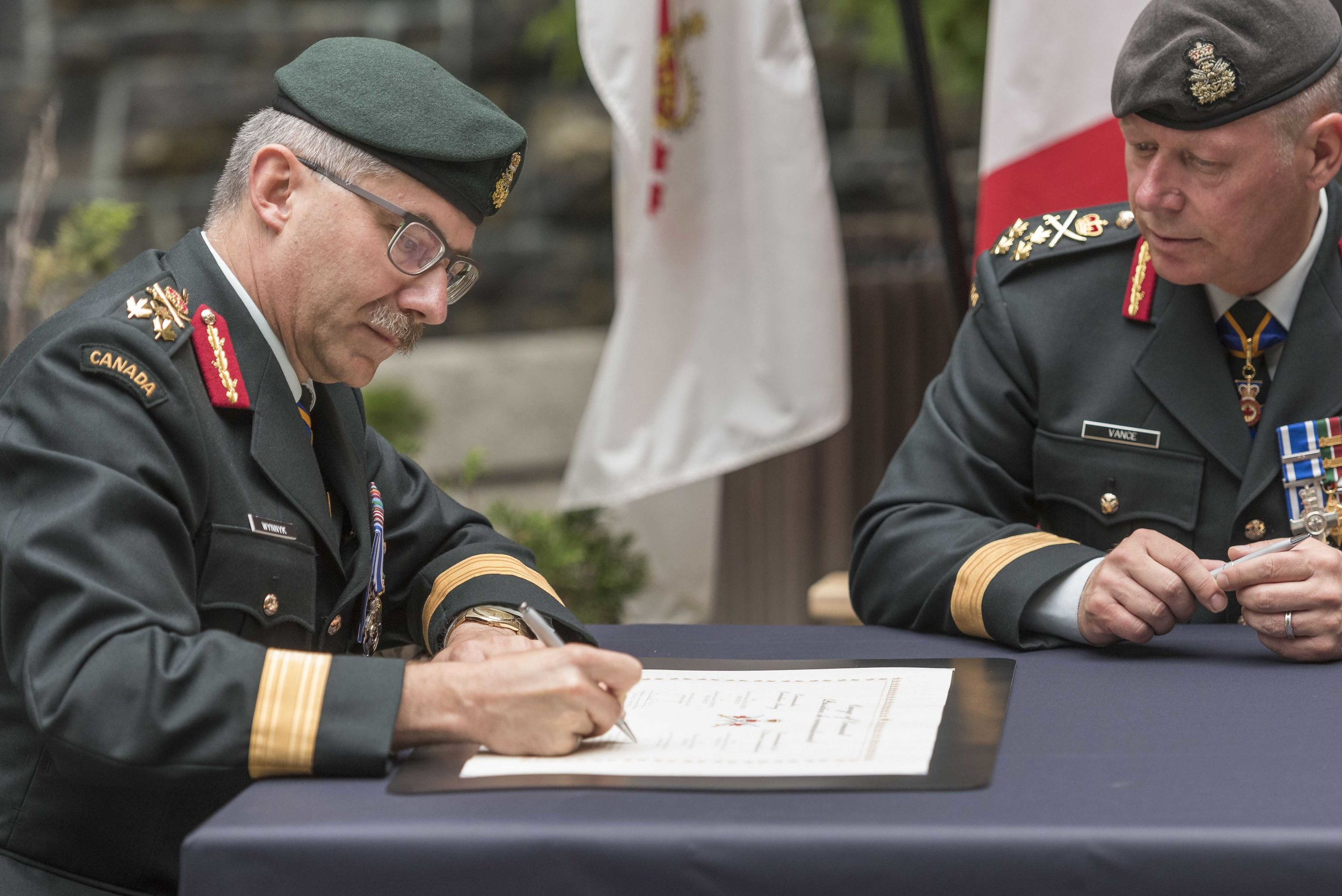 With Chief of Defence Staff General Jonathan Vance (right) looking on, LGen Paul Wynnyk (left) signs the official scroll that hands over the leadership of the Canadian Army to him from his predecessor, LGen Hainse, during the Commander Canadian Army Change of Command Ceremony. (cpl andrew wesley, directorate army public affairs)