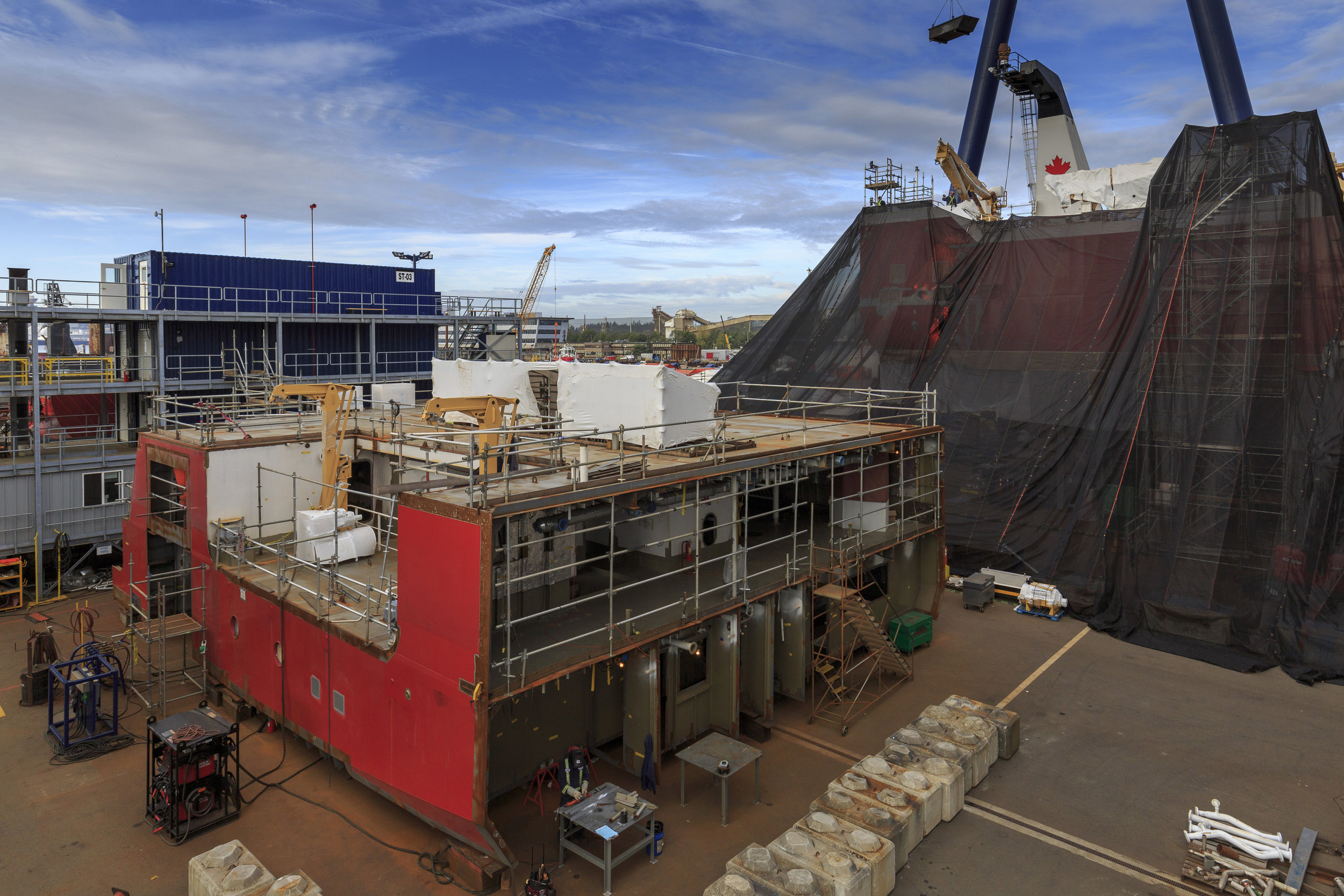 Seaspan Shipyards was awarded the non-combat package under the National Shipbuilding Strategy, which includes three Offshore Fisheries Science Vessels (OFSVs), one Offshore Oceanographic Science Vessel and one Polar Icebreaker for the Canadian Coast Guard and two Joint Support Ships for the Royal Canadian Navy. All three of the CCG's OFSVs are currently under construction at Seaspan, with each at various stages in their modular block construction. The first OFSV to be completed, the Sir John Franklin (behind the screen in the background), is scheduled for launch in December 2017.