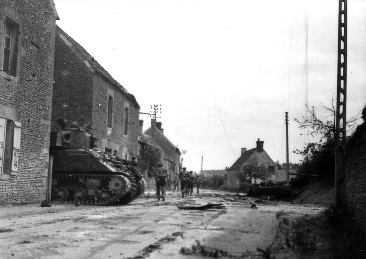 This August 19, 1944 photograph illustrates the close cooperation between the armour of the 29th Reconnaissance Regiment (South Alberta Regiment) and the infantrymen of the Argyll and Sutherland Highlanders of Canada. Protected but able to give support, a Sherman M4 tank lurks in a laneway while an infantry section advances along the roadside. (lt donald grant, dnd, library and archives canada)