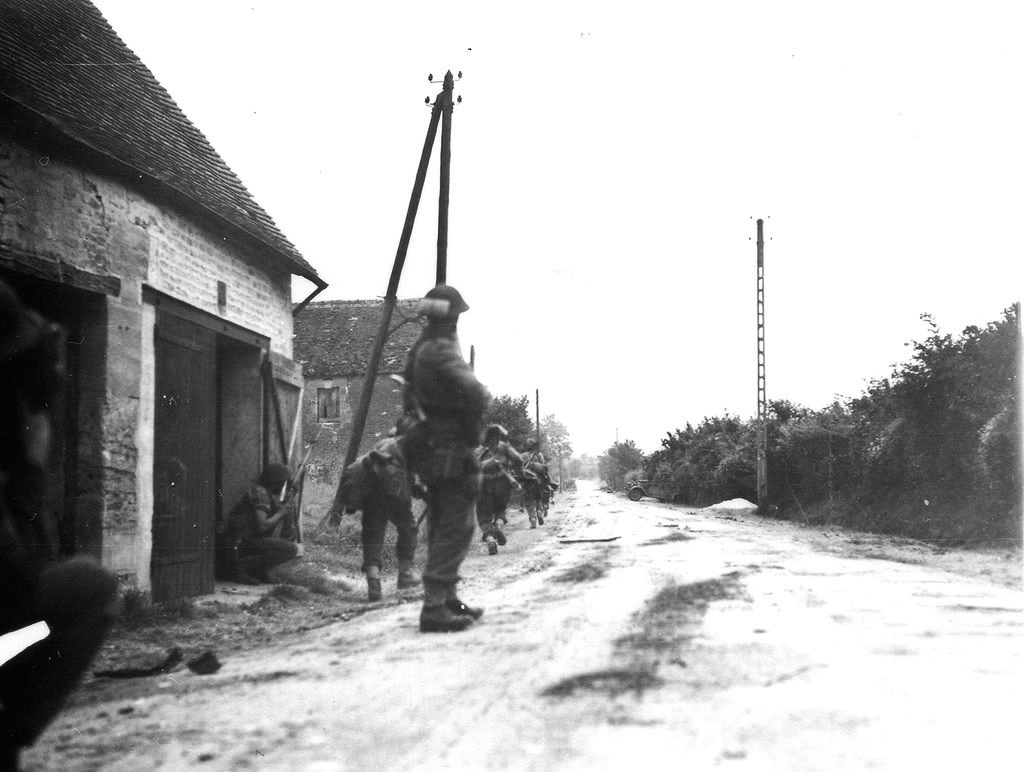 An infantry section of the ASH hustles down the verge of a laneway on the edge of St Lambert-sur-Dives. Note the field dressing under the mesh on the helmet of the figure mid-shot. (lt grant, dnd, lac)