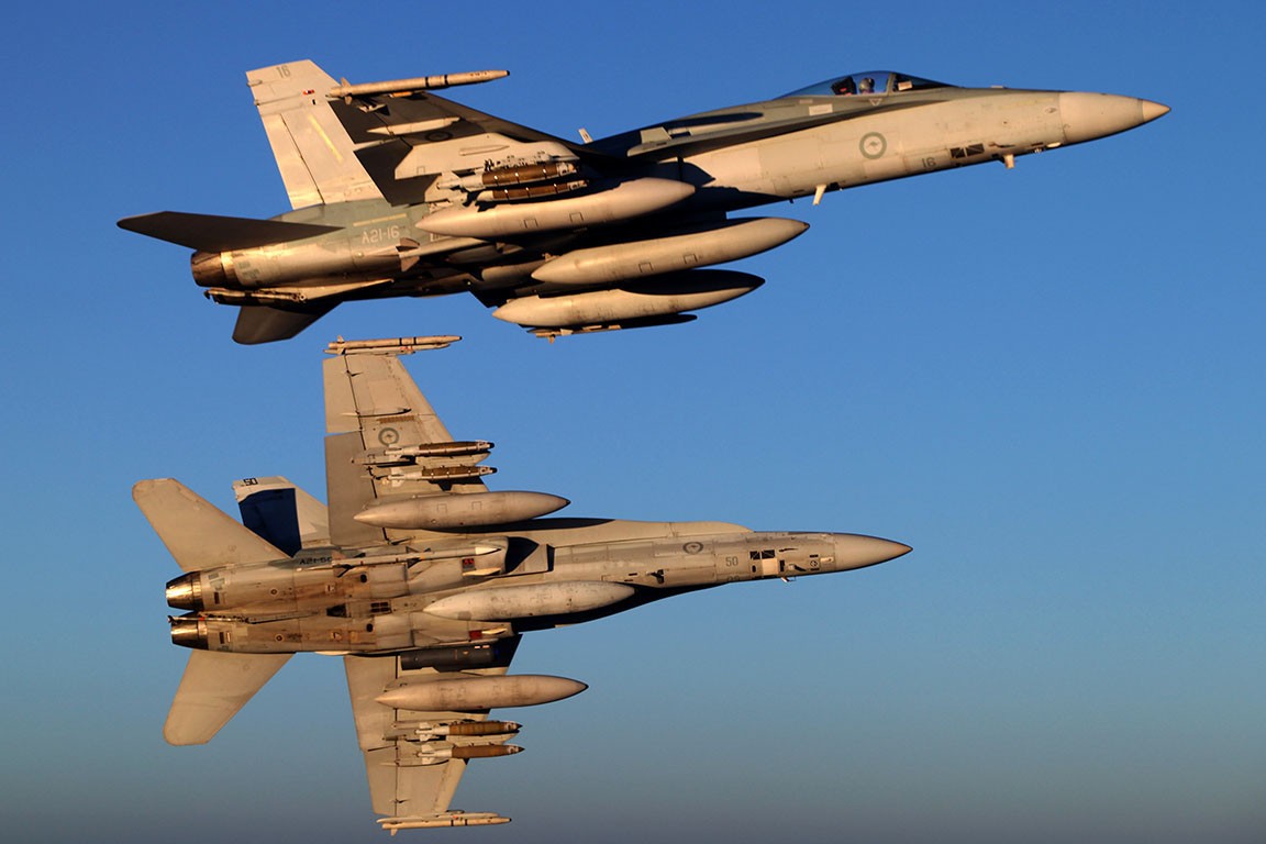 Royal Australian Air Force (RAAF) F/A-18A Hornets bank away. Canadian officials visited the RAAF in August 2017 to review the possibility of purchasing their used F-18s. (australian department of defence)