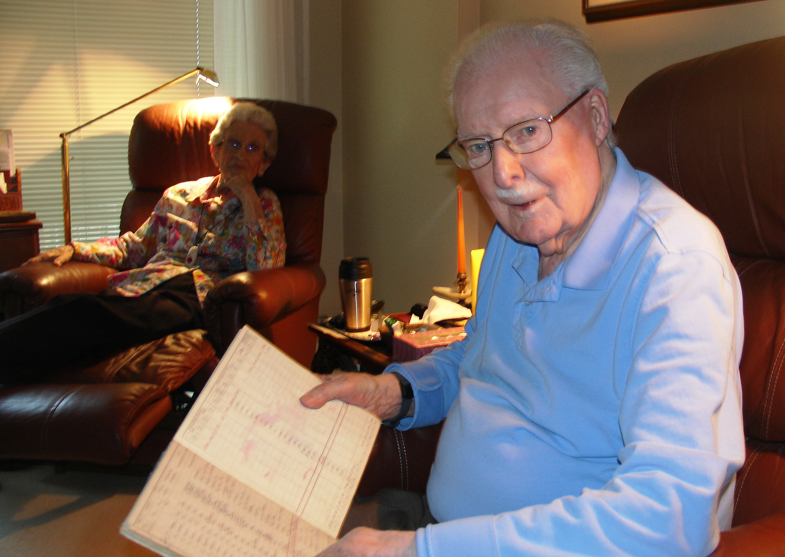 In this 2014 photo, Cliff Black is seen reviewing his old pilot's log book, which showed his entry for September 22, 1941, the day he spotted the wreckage of Anson N9818 near the peak of Old Settler Mountain, as his wife Sue looks on.