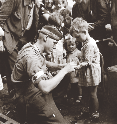 Private G.R. MacDonald of 2nd Division's Toronto Scottish (MG) gives first aid to an injured French boy in Brionne on August 25, 1944. (ken bell, pa–  135956  )