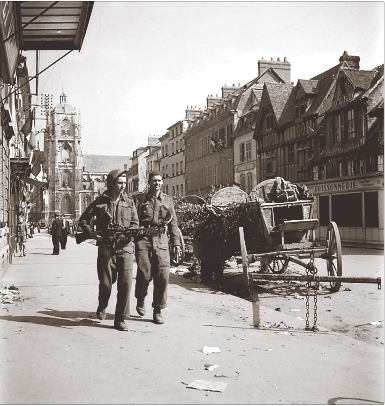 Royal Hamilton Light Infantry soldiers on patrol pass abandoned German wagons in Elbeuf on August 27, 1944. (ken bell, pa–  138276  )