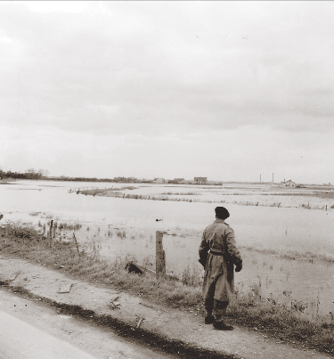 A Canadian soldier examines the inundated area southeast of Calais that funnelled Operation UNDERGO's line of advance toward the coastal approaches. (donald i. grant, pa–  131247  )