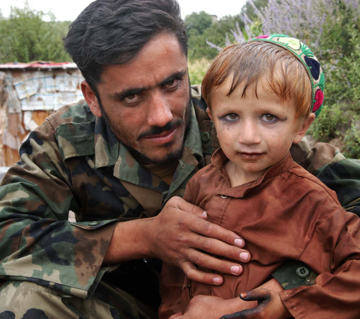 Afghan Security Force with pre-pubescent Afghan bacha boy