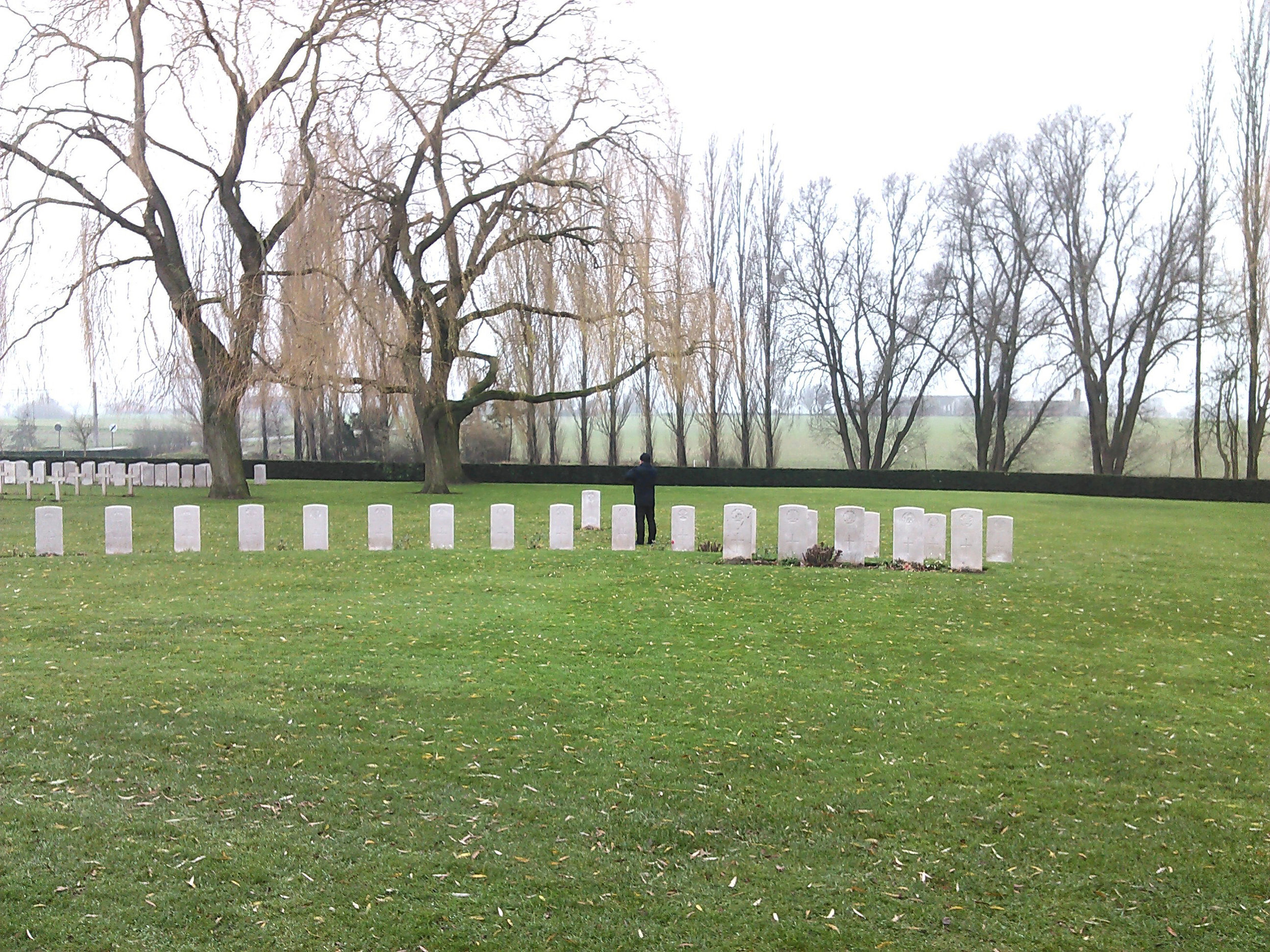British historian Stephen Brumwell stops to examine a grave in the Lijssenthoek Military Cemetery, a Belgian hamlet located about 12 km west of Ypres. Situated on the main communication line between the Allied military bases in the rear and the Ypres battlefields — close to the front but out of the extreme range of German field artillery — Lijssenthoek was a natural place to establish several casualty clearing stations.