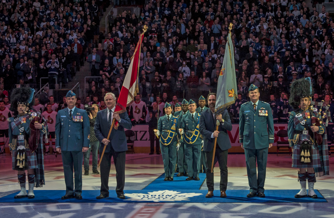 """The RCAF's retired Colours were entrusted to the guardianship of the Toronto Maple Leafs on February 10, 2018. From left are Lieutenant-Colonel (retired) Kenneth J. Mackenzie of the RCAF Pipes and Drums, Chief Warrant Officer Gérard Poitras, Darryl Sittler, holding the Queen's Colour, Darcy Tucker, holding the Command Colour, Lieutenant-General Mike Hood, and Major Allan J. MacKenzie of the RCAF Pipes and Drums (the two pipers are brothers). In the background is the Colours party from 402 """"City of Winnipeg"""" Squadron, with the officers saluting with drawn swords. PHOTO: Corporal Alana Morin, FA03-2018-0015-002"""