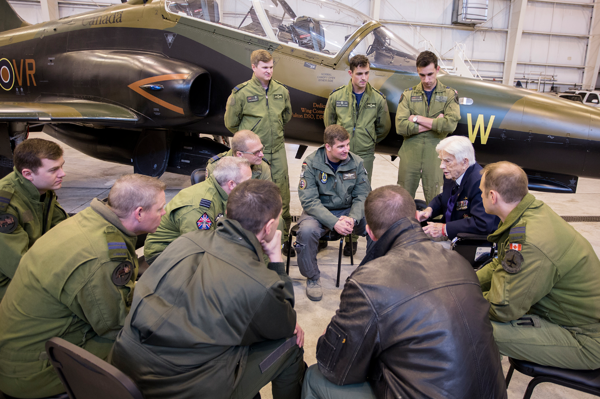 Members of RCAF 419 Tactical Fighter (Training) Squadron listen as RCAF Squadron Leader (retired) George Sweanor, talks about being one of the founding members of No. 419 Squadron, Royal Canadian Air Force, which stood up in the United Kingdom in 1941. In the background is one of the seven CT-155 Hawk jets flown by the squadron, this one sporting a special Second World War paint scheme. PHOTO: NORAD/USNORTHCOM Public Affairs
