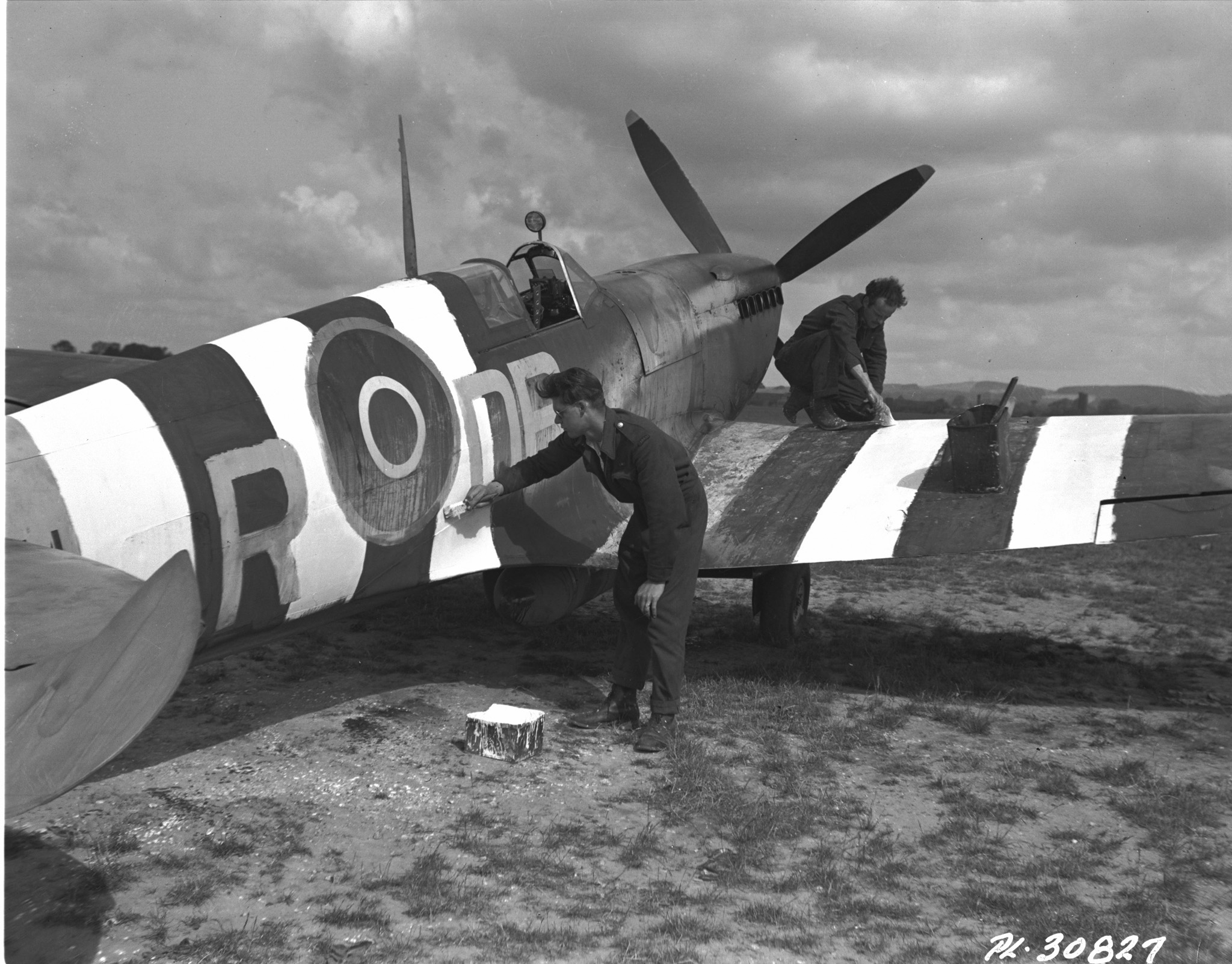 "These two RCAF men had a big job on their hands, painting the black and white recognition design on allied aircraft in advance of the D-Day assault. The Spitfire in the picture belonged to No. 402 ""Bear"" Squadron, one of the Canadian fighter wings. (dnd)"