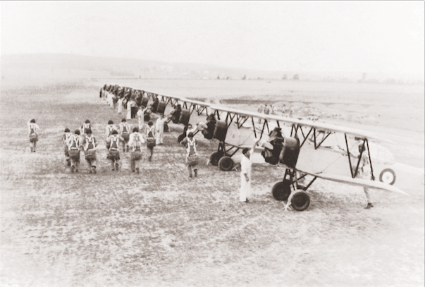 """British Commonwealth Air Training Plan (BCATP) students make their way toward Fleet Finch biplanes at an elementary flying school in Windsor Mills, Quebec. Over 400 Finches were built by Fleet Aircraft Limited of Fort Erie, Ontario between 1939 and 1941, and used as trainers for the Elementary Flying Training Schools. All BCATP and """"home squadron"""" aircraft belonged to the Canadian government, unlike many of those flown overseas by RCAF squadrons. (library and archives canada, pl-  2039  )"""