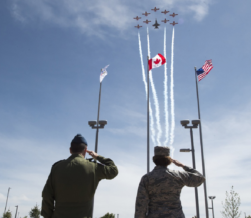 Royal Canadian Air Force Lieutenant-General Pierre St-Amand (left), NORAD Deputy Commander, and U.S. Air Force General Lori Robinson, NORAD Commander and Commander of U.S. Northern Command, and salute during the playing of the Last Post and a missing-man formation flyover carried out by the Canadian Forces Snowbirds on Peterson Air Force Base, Colorado, on May 11, 2018. The ceremony was part of the placement and dedication of a cairn to honor the Canadian service men and women who have died while serving with NORAD. The placement of the cairn was conducted in conjunction with the celebration of NORAD's 60th anniversary. PHOTO: U.S. DoD, Technical Sergeant Joe Laws