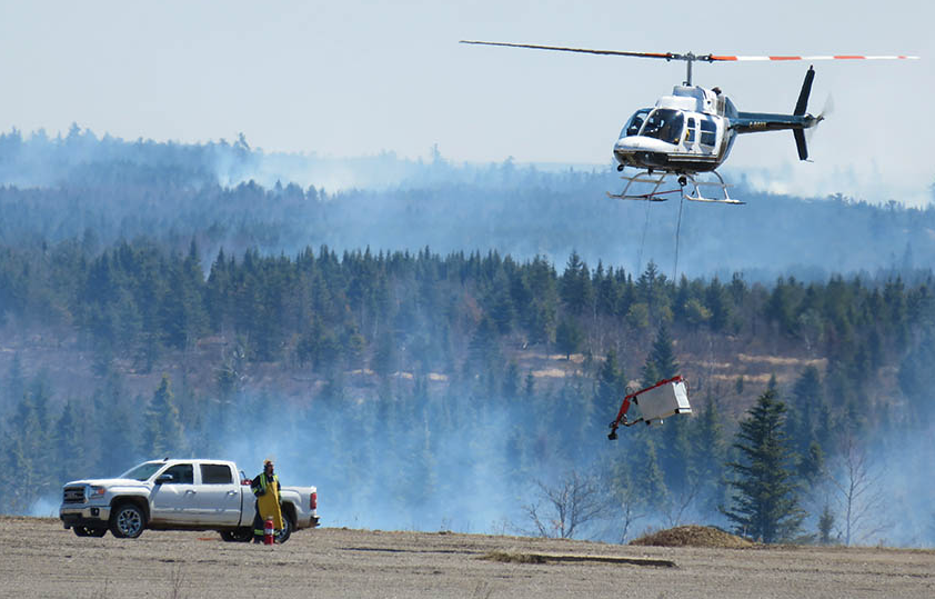 Firefighters from 5th Canadian Division Support Base Gagetown in New Brunswick are assisted by a civilian helicopter during the annual spring grass burn in April 2016. The aim of the program is to diminish the likelihood of grass fires occurring later in the season when conditions are drier and the fire hazard is much higher. Photo: Doug Wilson, Operations Services Branch Gagetown. ©2018 DND/MDN Canada.