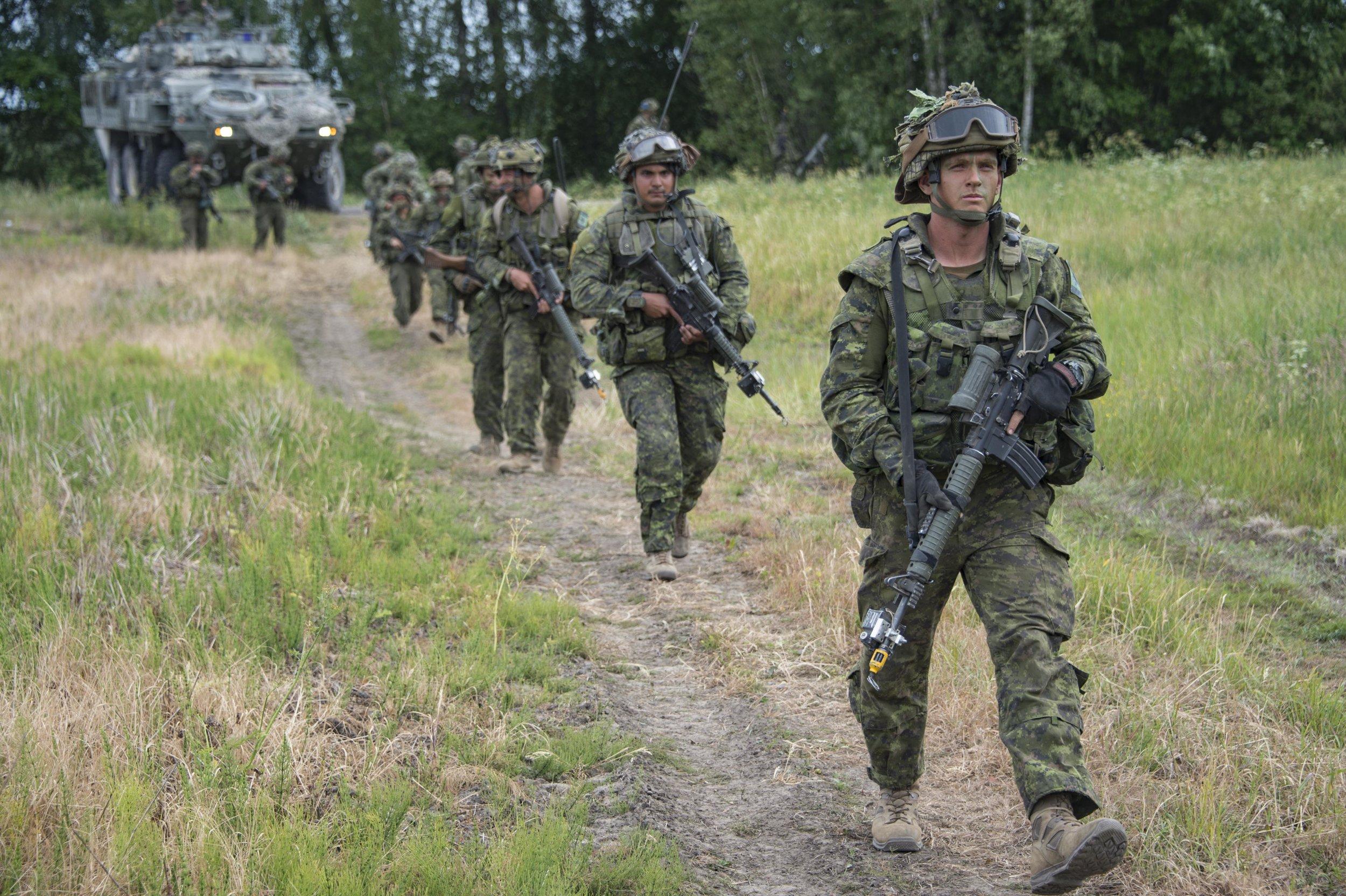 Canadian soldiers from India Company, enhanced Forward Presence Battle Group Latvia, move toward the woods during Exercise SABER STRIKE 2018, near Skrunda, Latvia on June 11, 2018. Photo: Cpl Jean-Roch Chabot, eFP BG LATVIA Public Affairs RP15-2018-0140-059