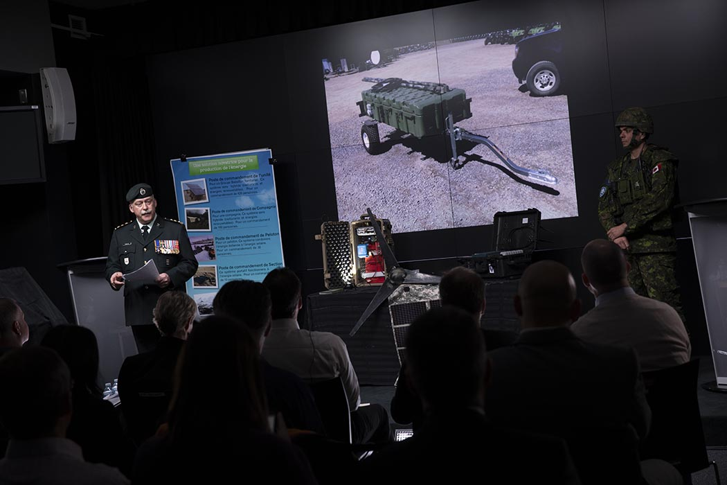 A team from 35 Canadian Brigade Group in Quebec has been awarded $1 million to develop a mobile solar- and wind energy-based system designed to keep batteries charged in the field when fuel resupply is not possible. Captain Pierre Frenette (left) led the group's presentation at a Dragon's Den-style competition held at National Defence Headquarters on November 30, 2018. Photo: Richard Guertin, Assistant Deputy Minister (Public Affairs). ©2018 DND/MDN Canada.