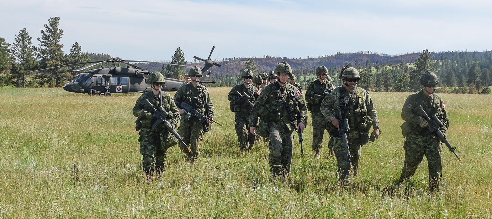 Corporal Jessica Bonner, a Reservist with 38 Service Battalion (left), with members of Task Force 38 Quick Reaction Force, tour the UH-60 Blackhawk helicopter from the G 2-211th Aviation Regiment of the Wyoming Army National Guard in Custer State Park, South Dakota on June 15, 2018 during Exercise GOLDEN COYOTE 2018. Photo: Second Lieutenant Natasha Tersigni, 38 Canadian Brigade Group Public Affairs. ©2018 DND/MDN Canada