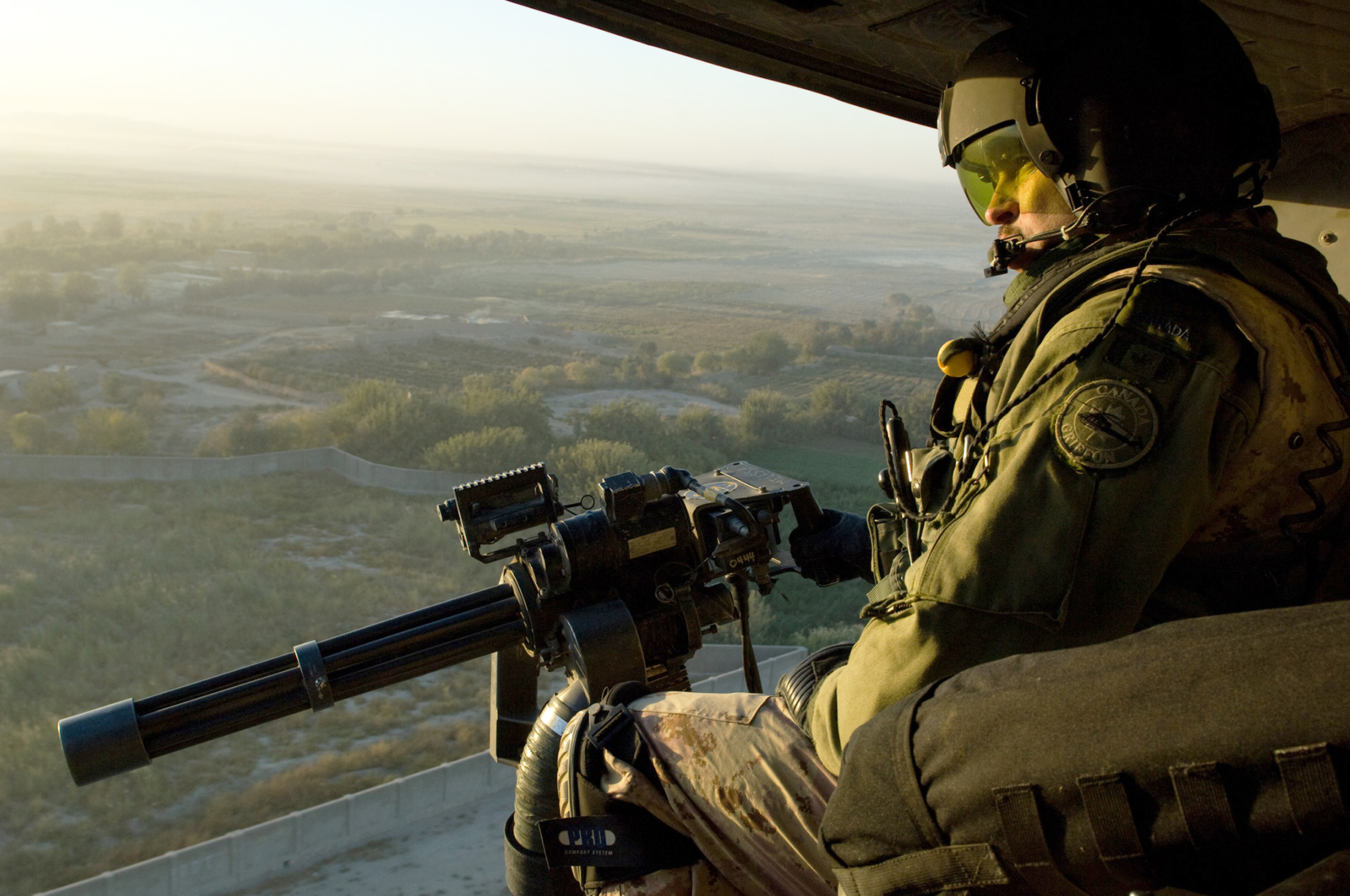 On October 13, 2009, during Roto 8 of Joint Task Force Afghanistan, flight engineer Corporal Steve J. Laing mans a Dillion 7.62mm M134 Minigun mounted on the side of a CH-146 Griffon helicopter during an early morning operation. PHOTO: Master Corporal Matthew McGregor, AR2009-0002-09
