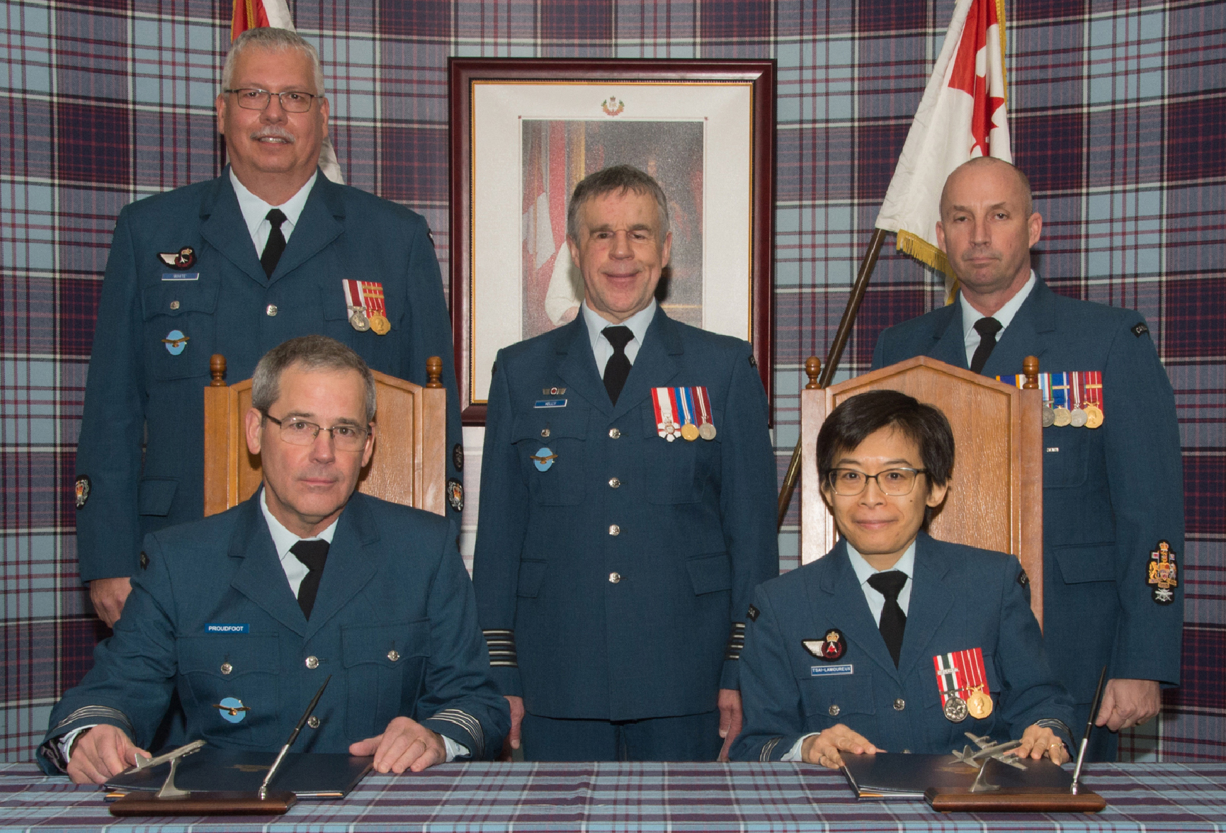 14 Air Maintenance Squadron Honorary Colonel David Proudfoot sits with squadron commander Lieutenant-Colonel Amy Tsai-Lamoureux during Honorary Colonel Proudfoot's investiture at 14 Wing Greenwood, Nova Scotia, on March 21, 2019. Standing, from left, are Master Warrant Officer Gord Morse, 14 Wing Honorary Colonel Terry Kelly, and Wing Chief Warrant Officer Dan Campbell. PHOTO: Leading Seaman Cassidy Moon, GD02-2019-0126-026