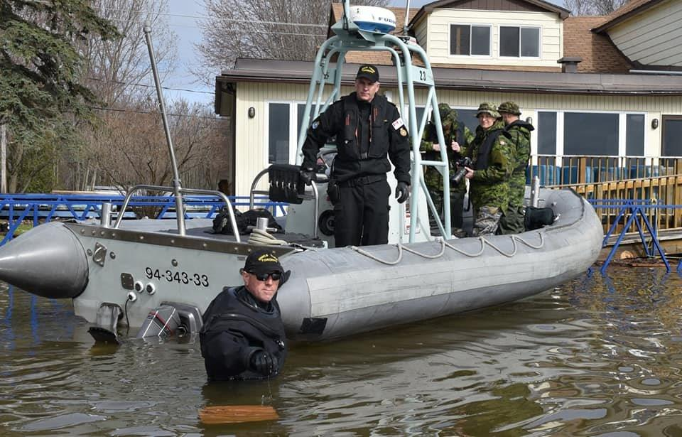 Master Seaman Curtis Kostin as boat coxswain for one of the small boats used to navigate the community of Sainte-Marthe-sur-le-Lac where 2,000 homes were flooded.