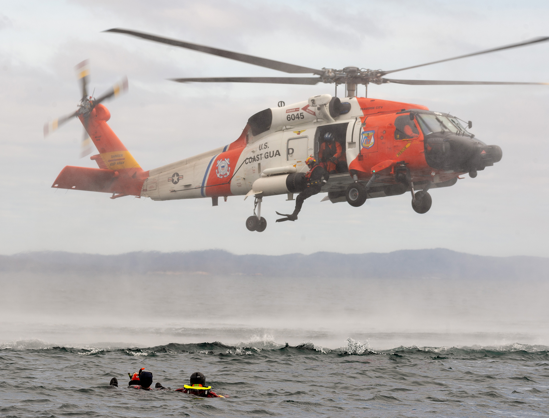 On May 6, 2019, a United States Coast Guard Rescue swimmer jumps from a U.S. HH-60 Jayhawk helicopter to rescue simulated casualties in the water as part of Chinthex 2019, near Thunder Bay, Ontario. PHOTO: Corporal Bryce Cooper, WG2019-0191-093