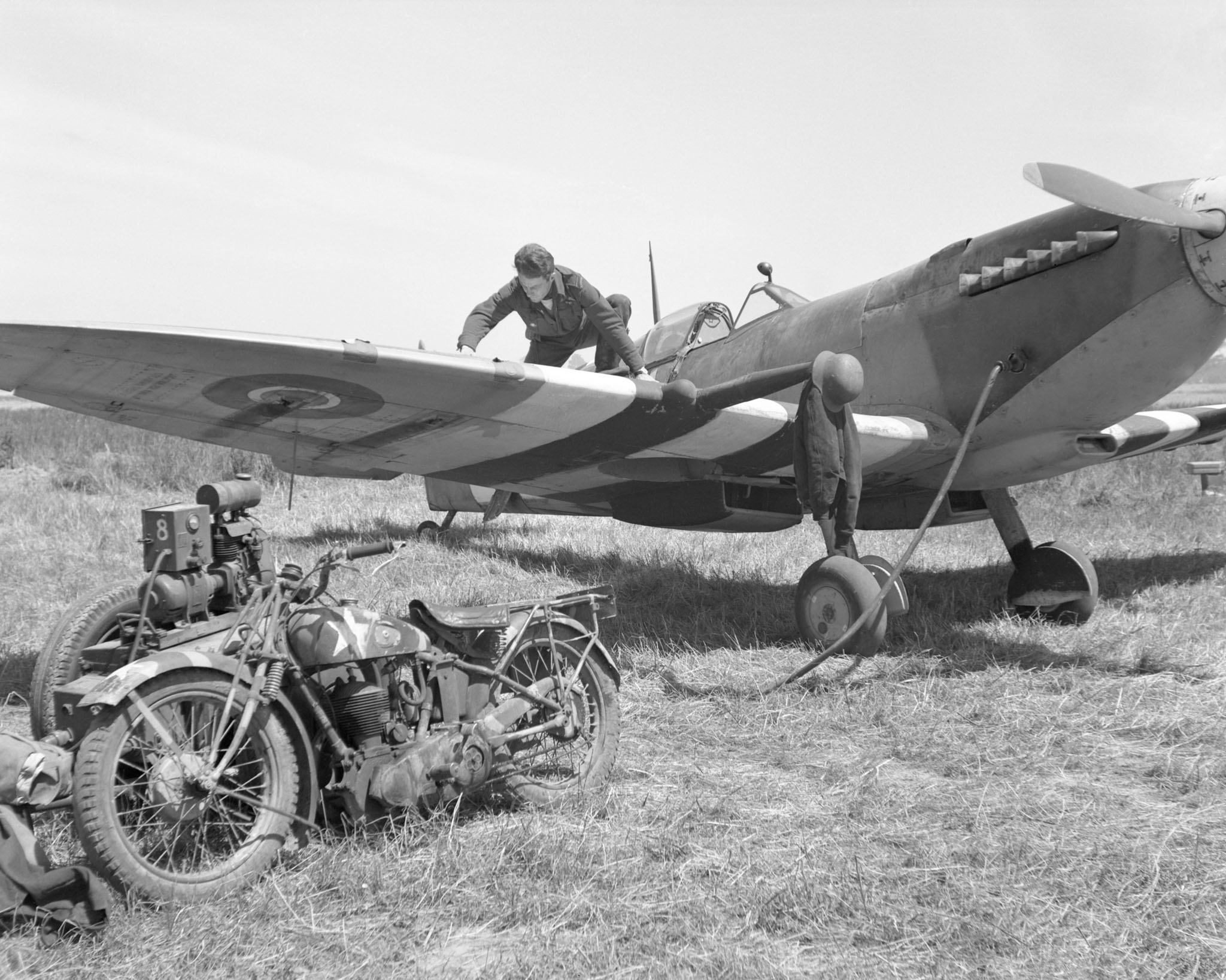 "The original caption of this photo, taken on June 8, 1944, reads: ""a captured German helmet over the muzzle of his cannon and a German motorbike obtained on a visit to the front line are now the property of Flying Officer H.W. 'Bud' Bowker [of] Granby, Quebec. He is seen here working on the guns of the Spitfire he flies with a Royal Canadian Air Force Squadron in France."" PHOTO: DND Archives, PL30259"